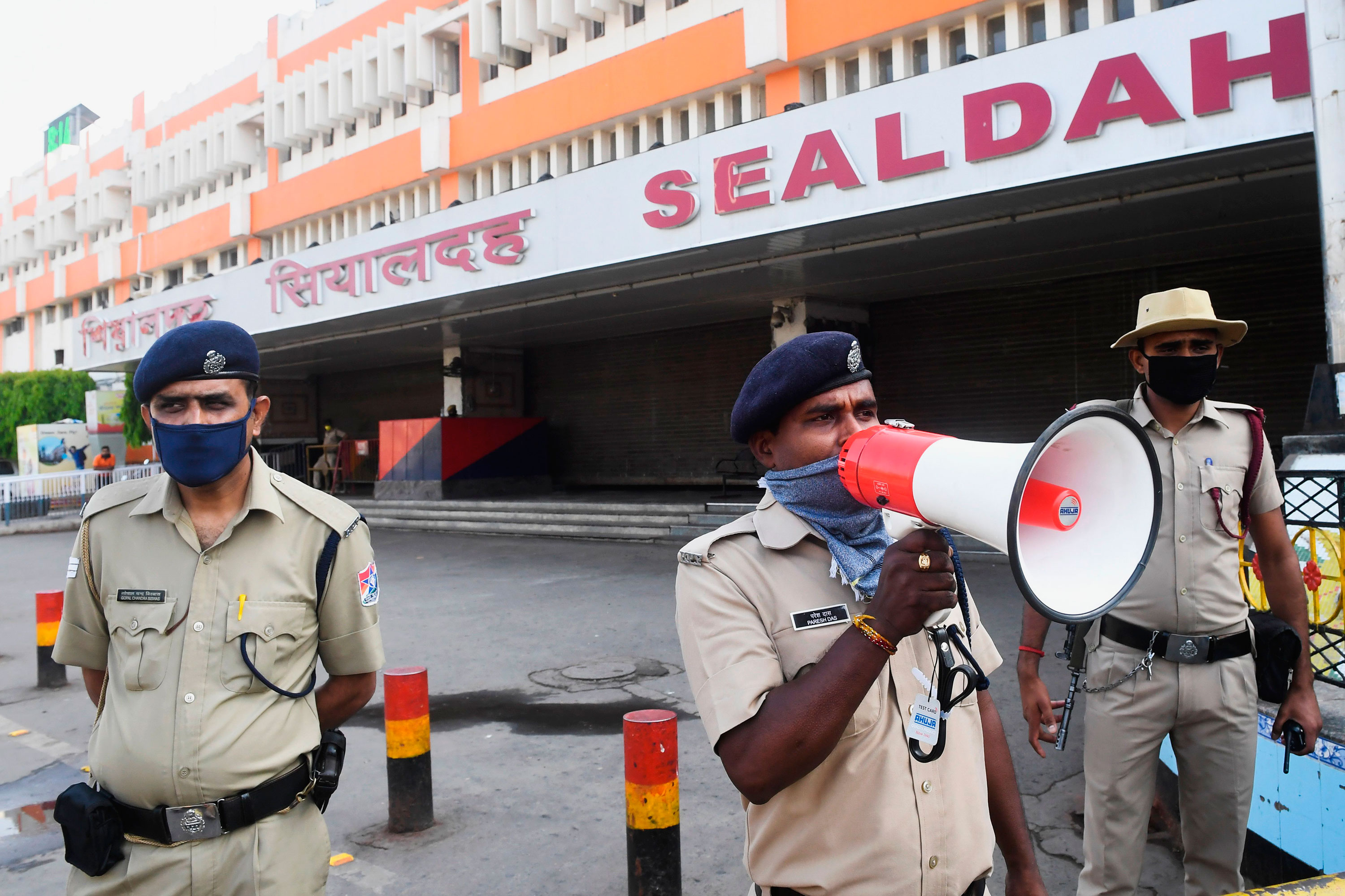 Railway Protection Force personnel announce the suspension of railway services through the end of month at Sealdah Railway station in Kolkata, India on March 23.