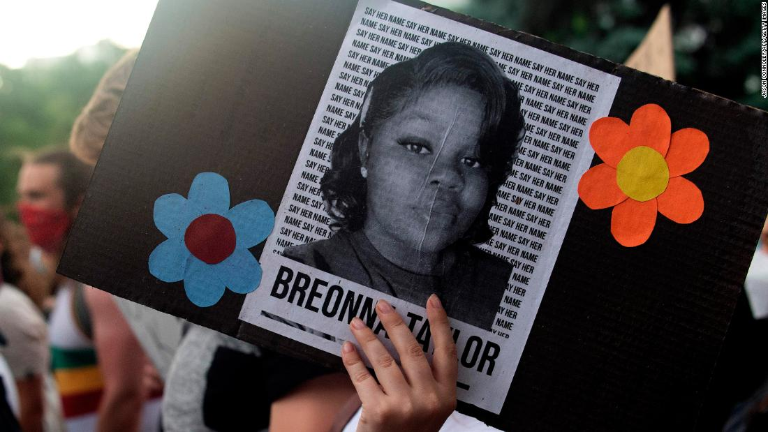A demonstrator holds a sign with the image of Breonna Taylor, a Black woman who was fatally shot by Louisville Metro Police Department officers.