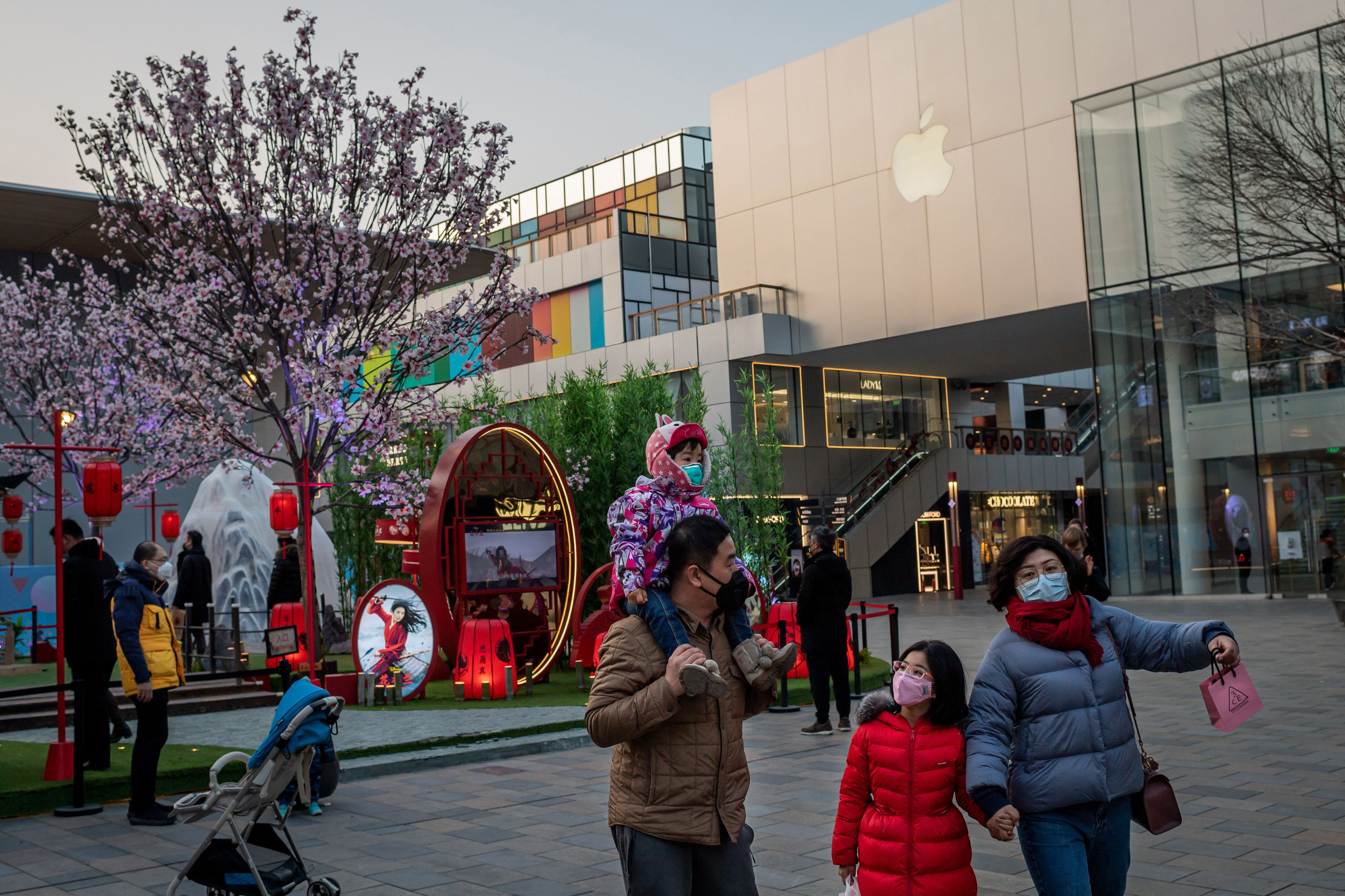 A family walks past an Apple store in Beijing on January 30.