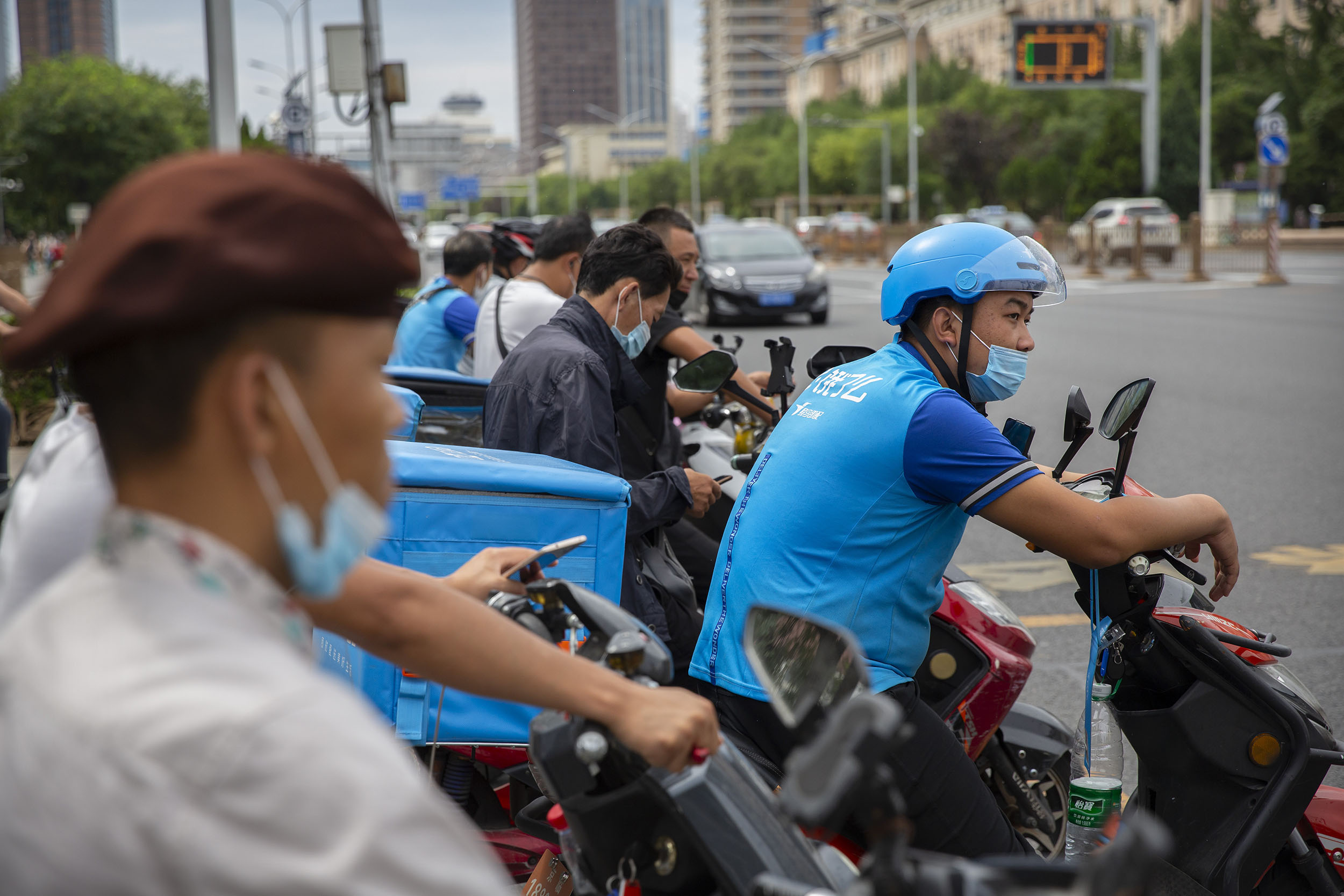 Delivery drivers wearing face masks to protect against the coronavirus wait to cross an intersection in Beijing, on Wednesday, August 19.