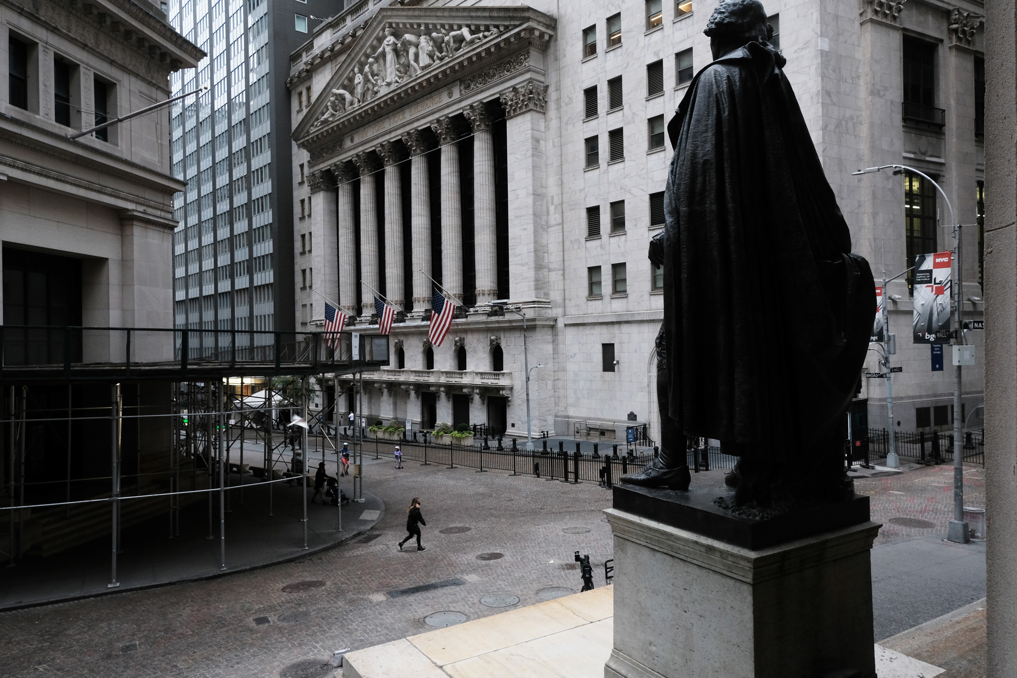 People walk by the New York Stock Exchange in lower Manhattan on October 2 in New York City.