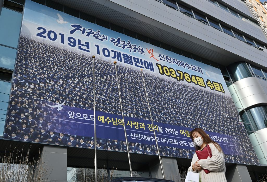 A woman wearing a face mask walks in front of the Daegu branch of the Shincheonji Church of Jesus in Daegu on February 27.