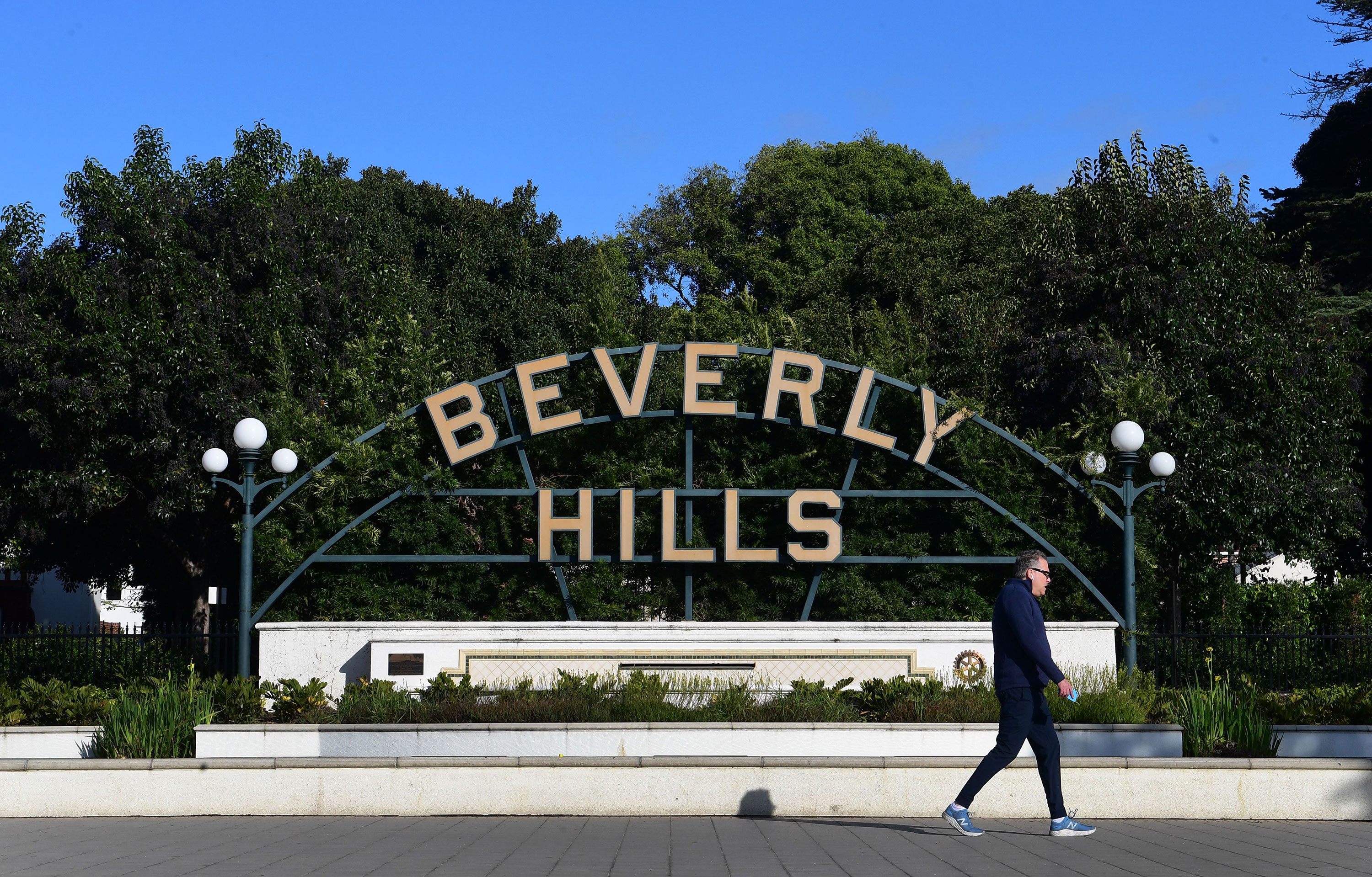 A man walks past the Beverly Hills sign on March 20 in California.