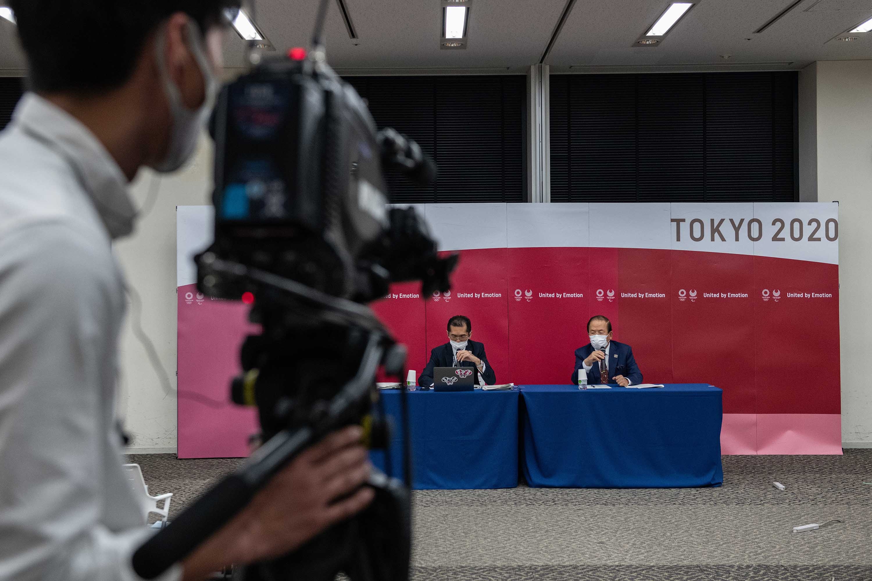 A camera person records as Toshiro Muto, Tokyo 2020 Olympic Games CEO, right, speaks during a press conference in Tokyo on December 22.