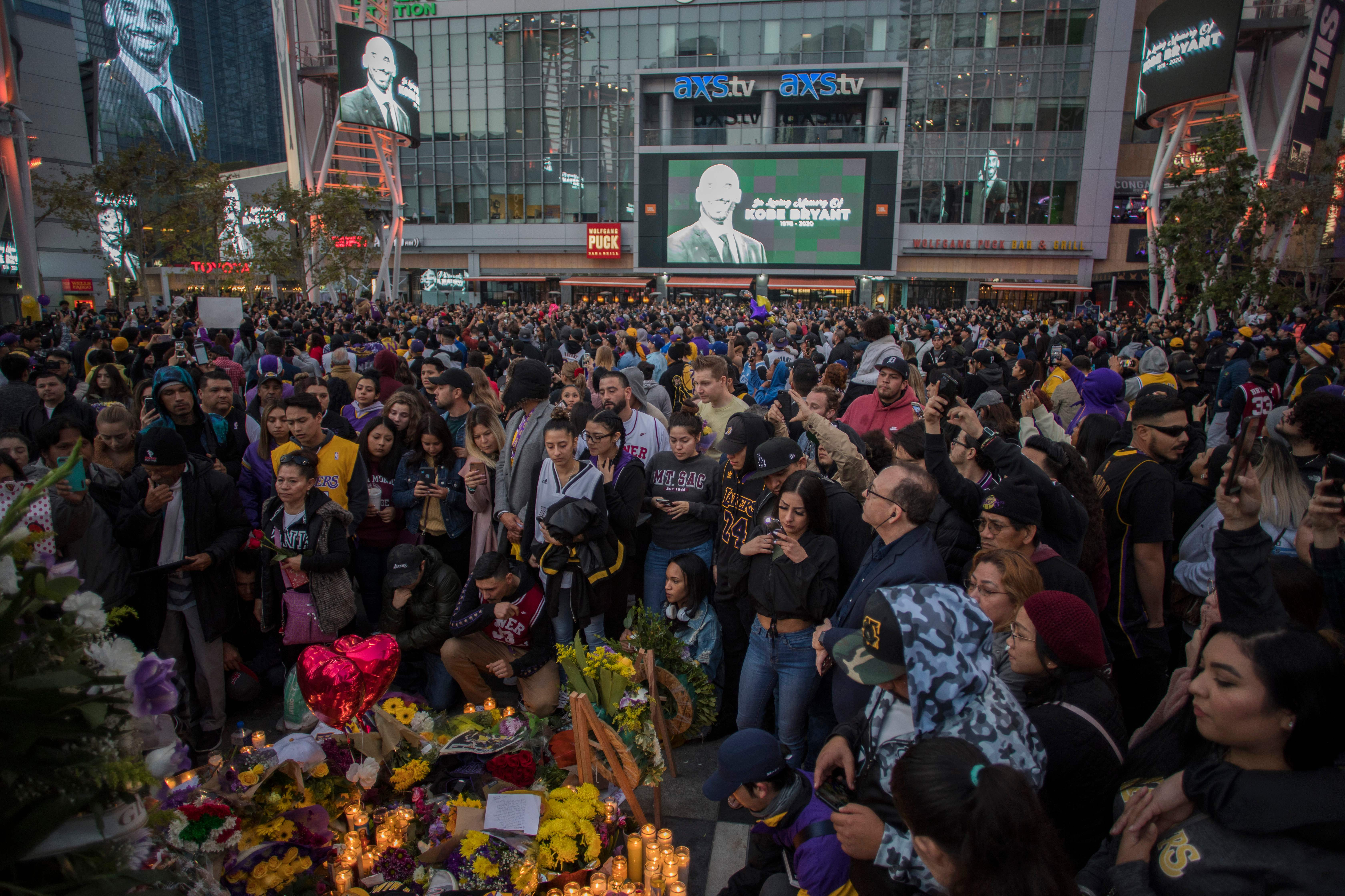 People gather around a makeshift memorial for Kobe Bryant in front of Staples Center in Los Angeles on January 26, 2020.