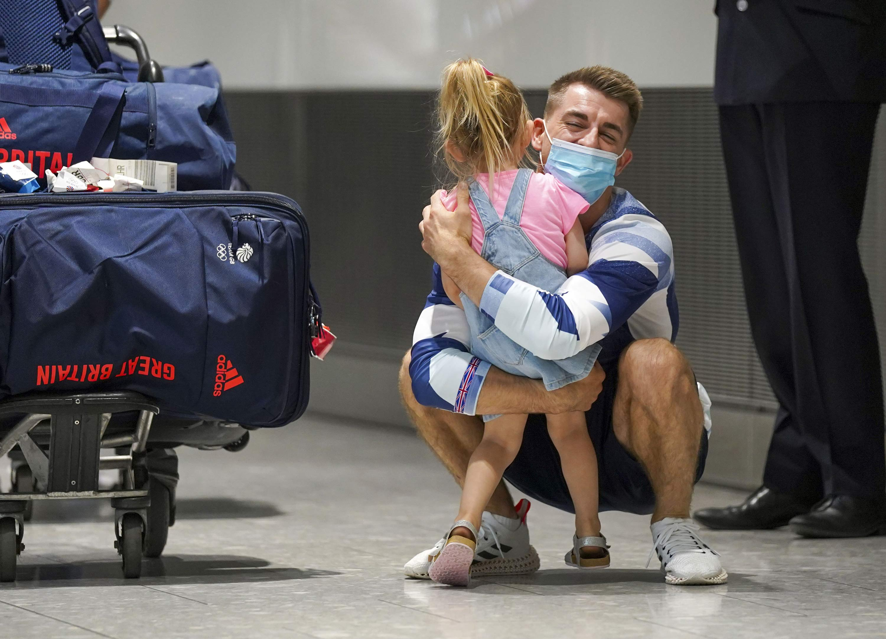 Olympic gymnast Max Whitlock hugs his daughter as he arrives back at London Heathrow Airport from the Tokyo 2020 Olympic Games on August 3.