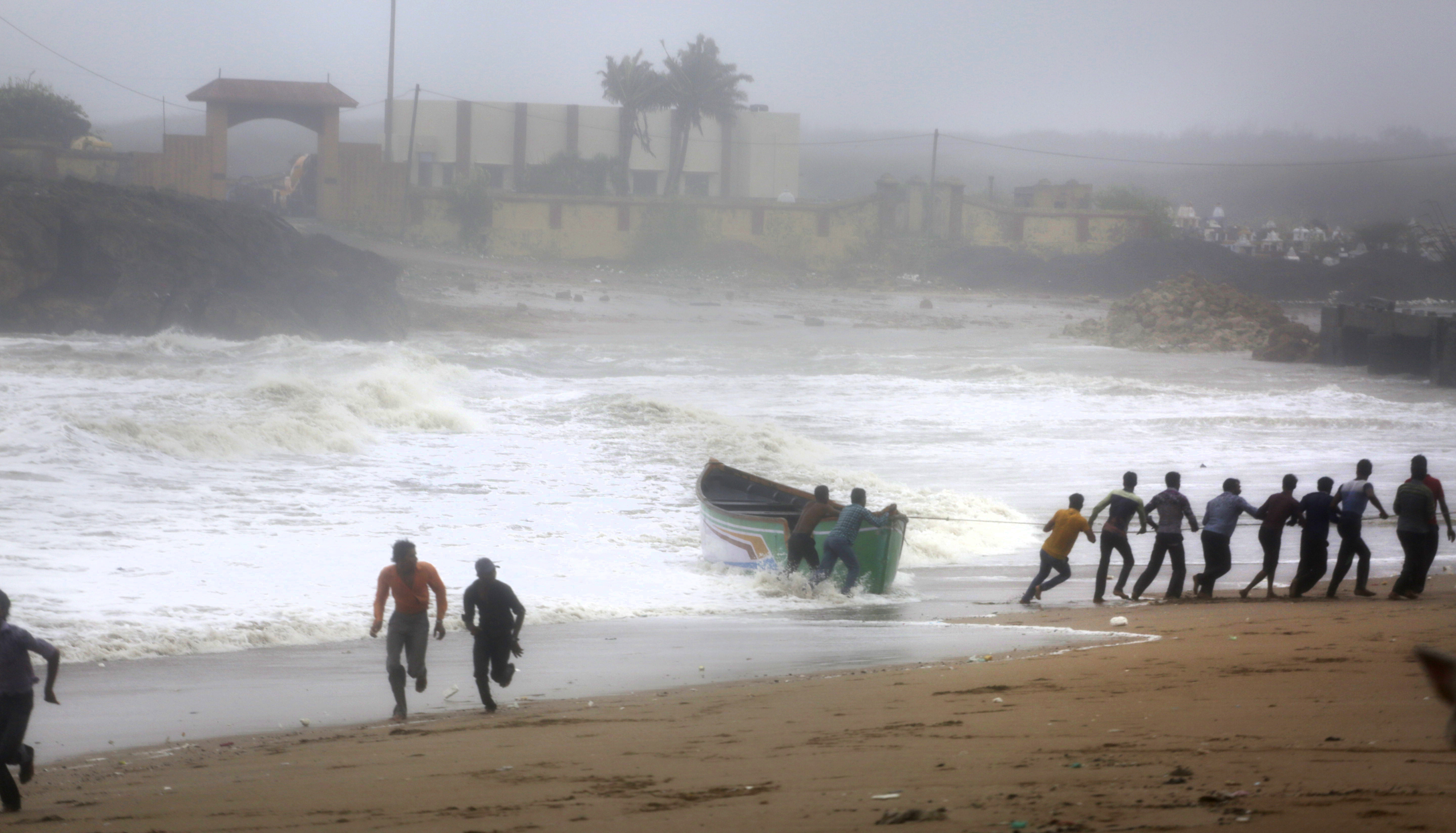 People try to pull back a fishing boat that was carries away by waves on the Arabian Sea coast as others run to take shelter in Veraval, India, on June 13, 2019.
