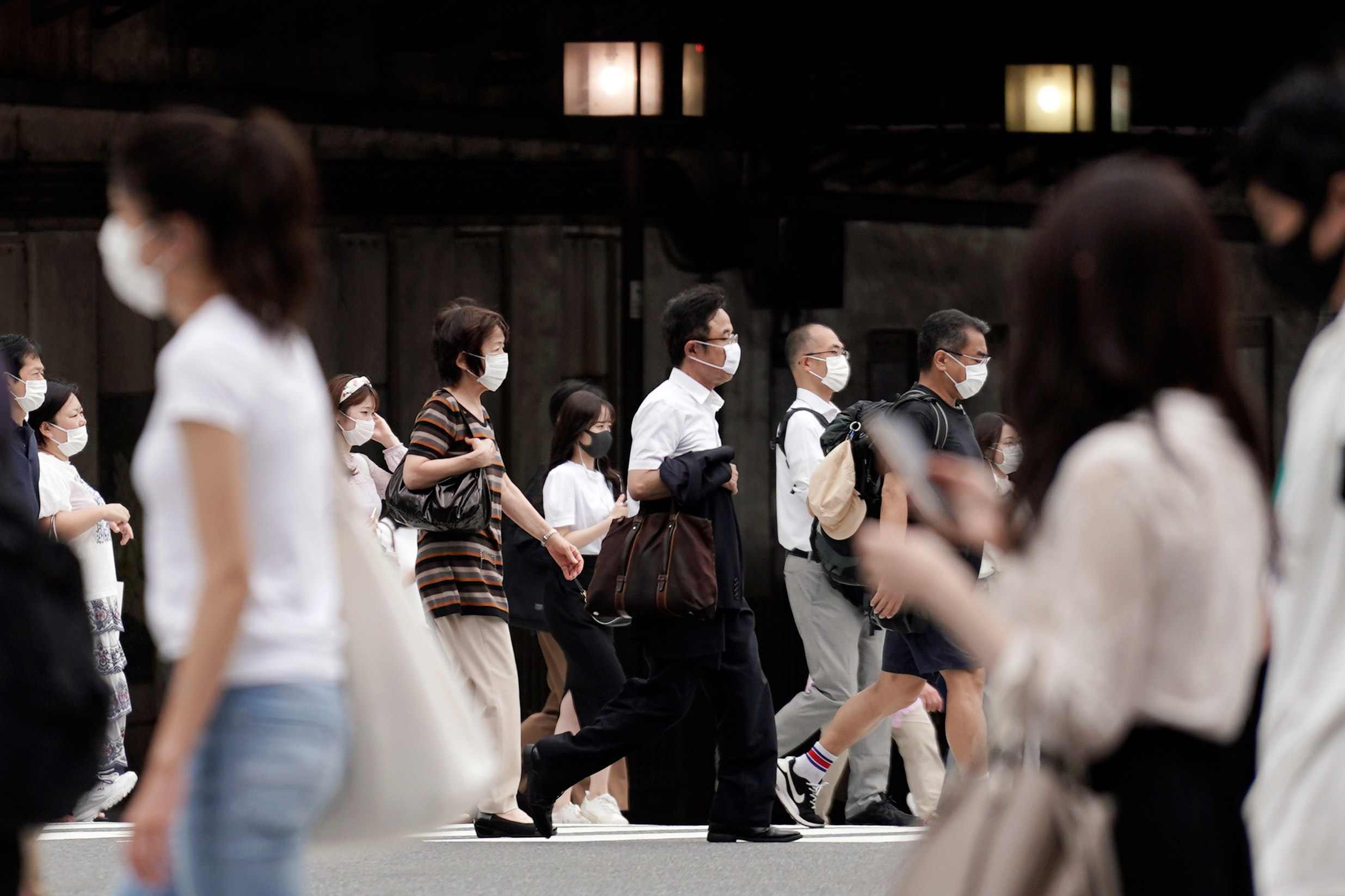 People walk at a pedestrian crossing on July 16 in Tokyo.