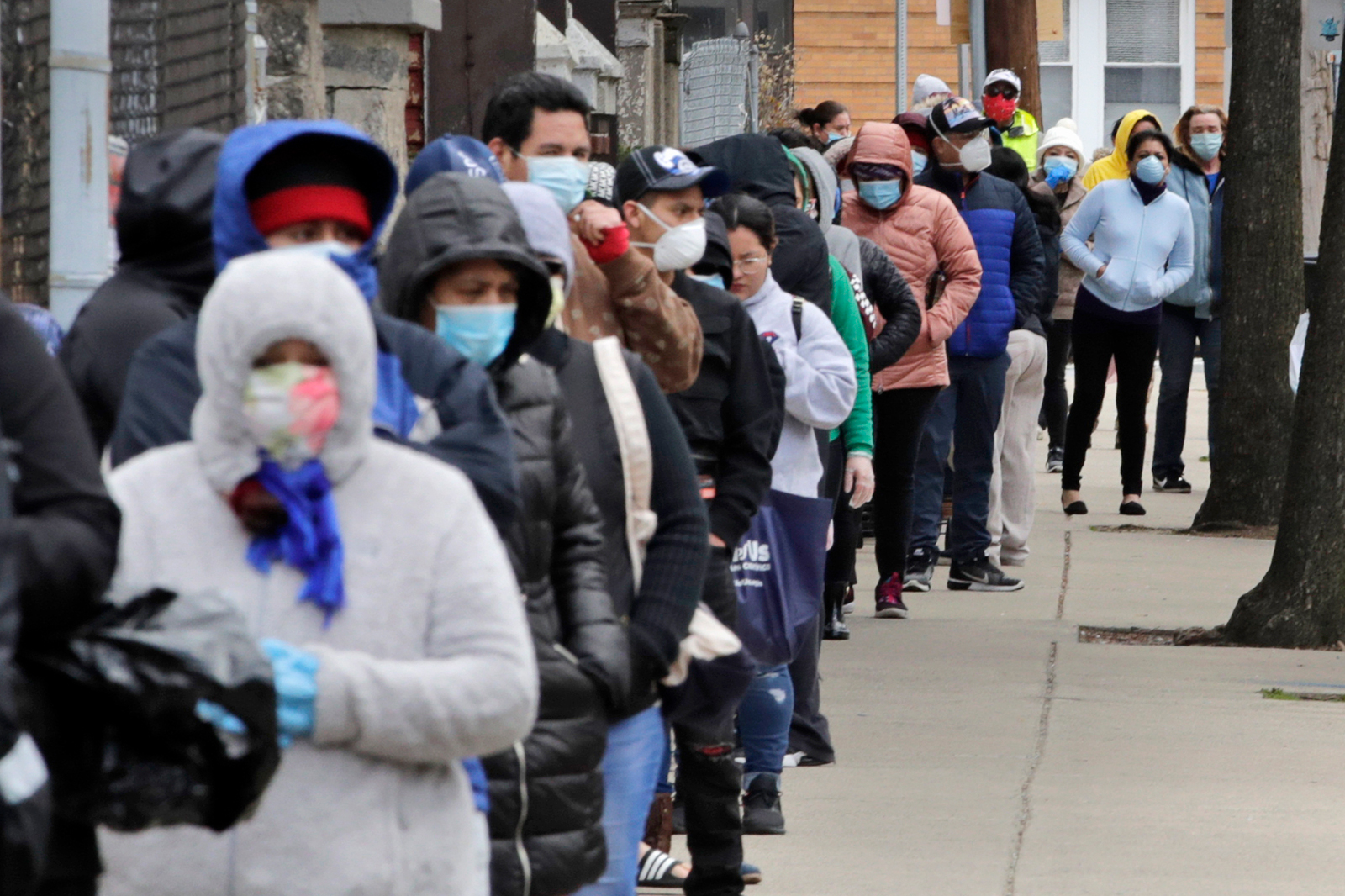 Hundreds impacted by the Covid-19 virus outbreak wait in line for boxes of food at a Salvation Army center in Chelsea, Mass., on April 22.