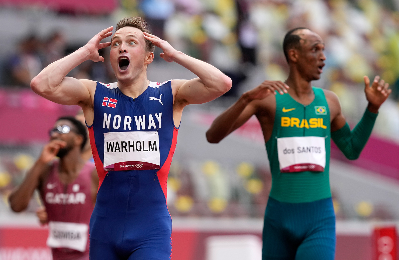 Norway's Karsten Warholm celebrates after winning the gold medal and breaking a world record in the 400 meter hurdles final on Tuesday.