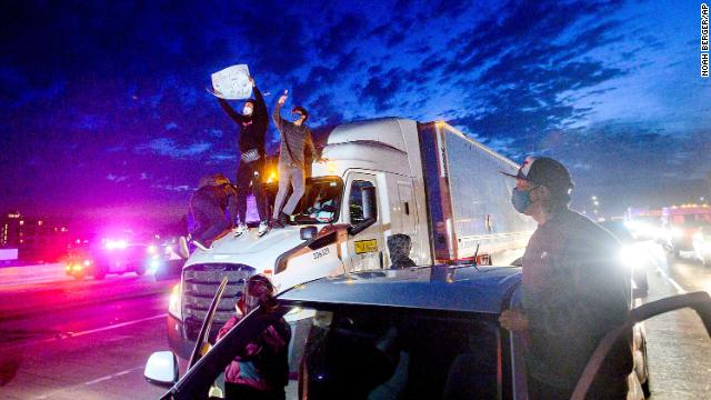 Demonstrators climb atop a truck while blocking traffic on Interstate 880 in Oakland, California, on May 29.