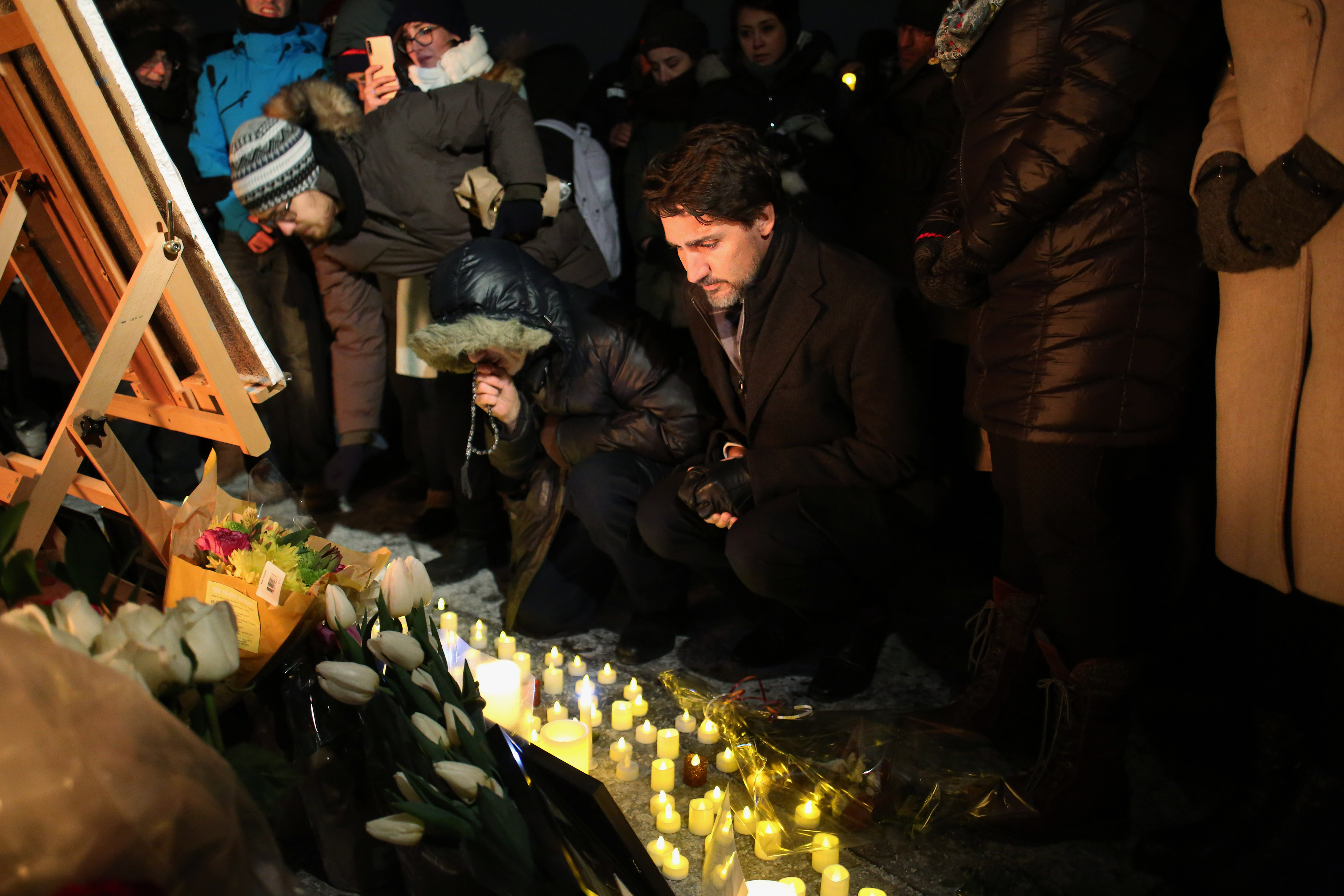 Canadian Prime Minister Justin Trudeau places a candle at vigil for victims of the a plane crash in Iran.