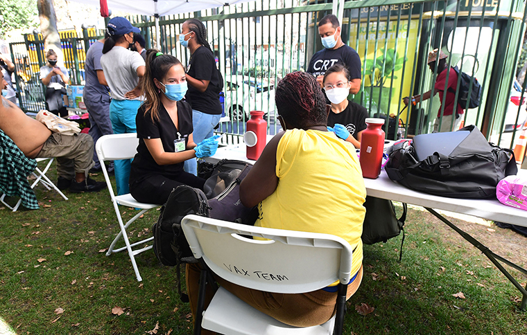Registered Nurses Amber Boyd, left,  and Darian Sumbingco, right, discuss concerns with a woman deciding to receive the Covid-19 vaccine at a vaccination clinic for homeless people, hosted by the Los Angeles County Department of Public Health and United Way on Wednesday, September 22, in Los Angeles.
