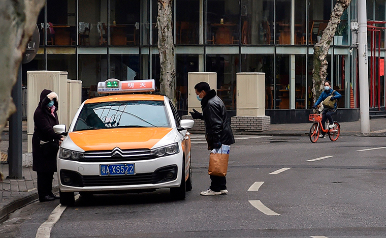 People wearing protective facemasks are seen while taking a taxi in Wuhan on January 26.