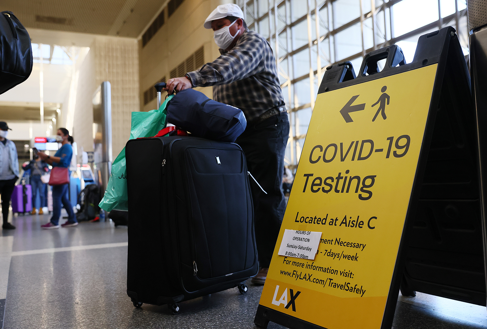 People wait in line to check in near a sign pointing to a Covid-19 testing area in the Tom Bradley International Terminal at Los Angeles International Airport (LAX) in California, on December 22, 2020.