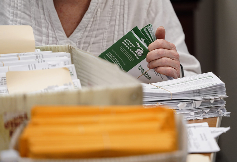 Elections volunteers count absentee elections ballots for the Michigan Primary election at Livonia City Hall in Livonia on Tuesday, March 10.