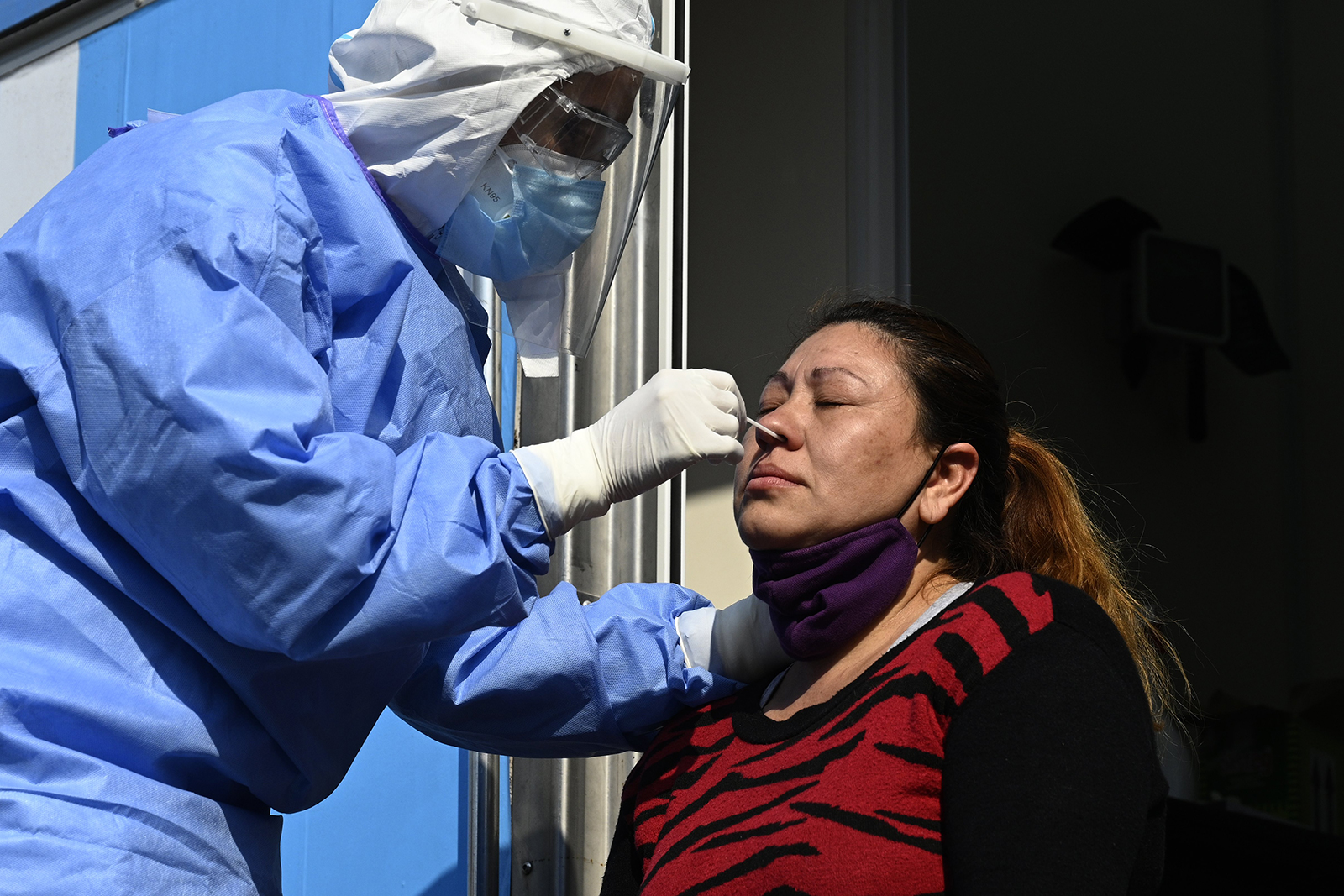 A doctor takes samples for a PCR test to a woman with Covid-19 symptoms at the mobile health unit in Villa Fiorito, Buenos Aires outskirts, Argentina, on August 3.