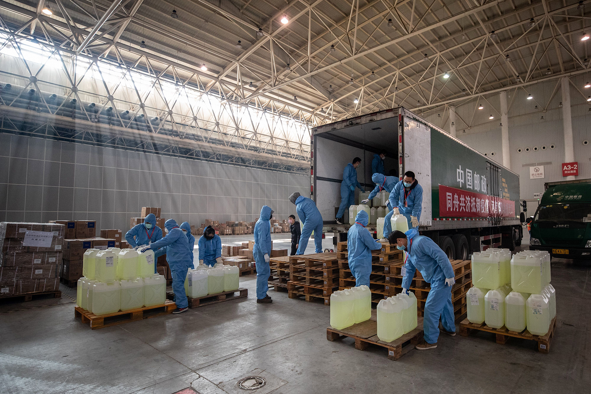 Staff members and volunteers transfer medical supplies from various sources at a warehouse of an exhibition center which has been converted into a makeshift hospital in Wuhan, on Tuesday.