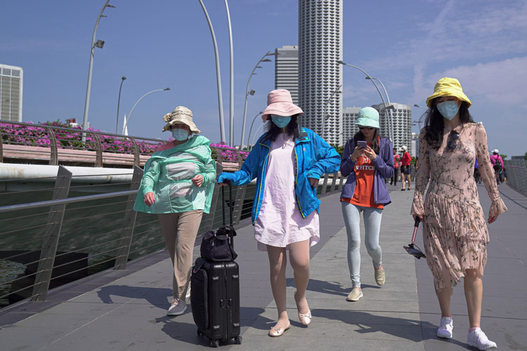 Visitors wearing masks walk through the Merlion Park in Singapore on January 26.