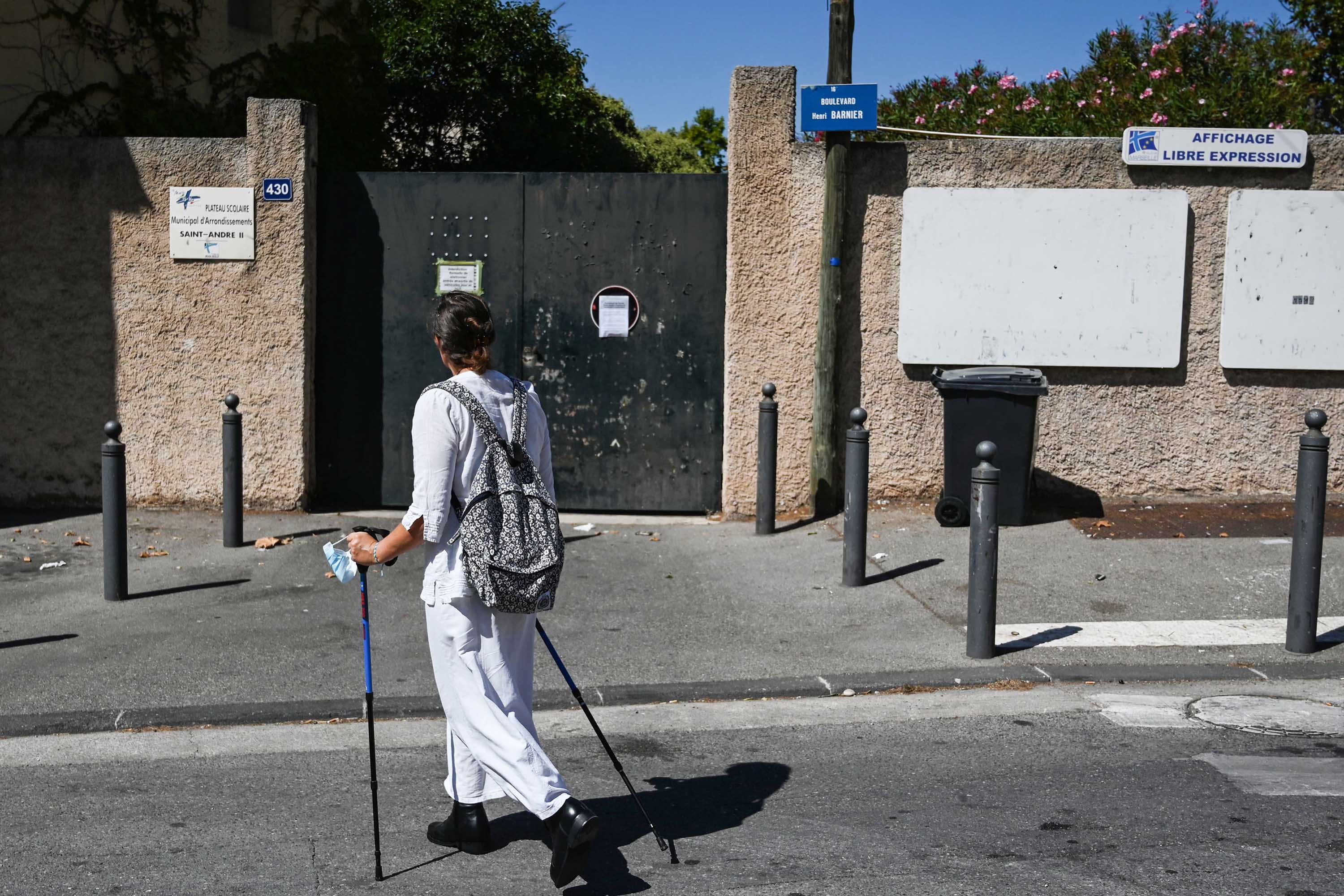 A woman walks in front of a closed primary school in the southern French city of Marseille on September 4.