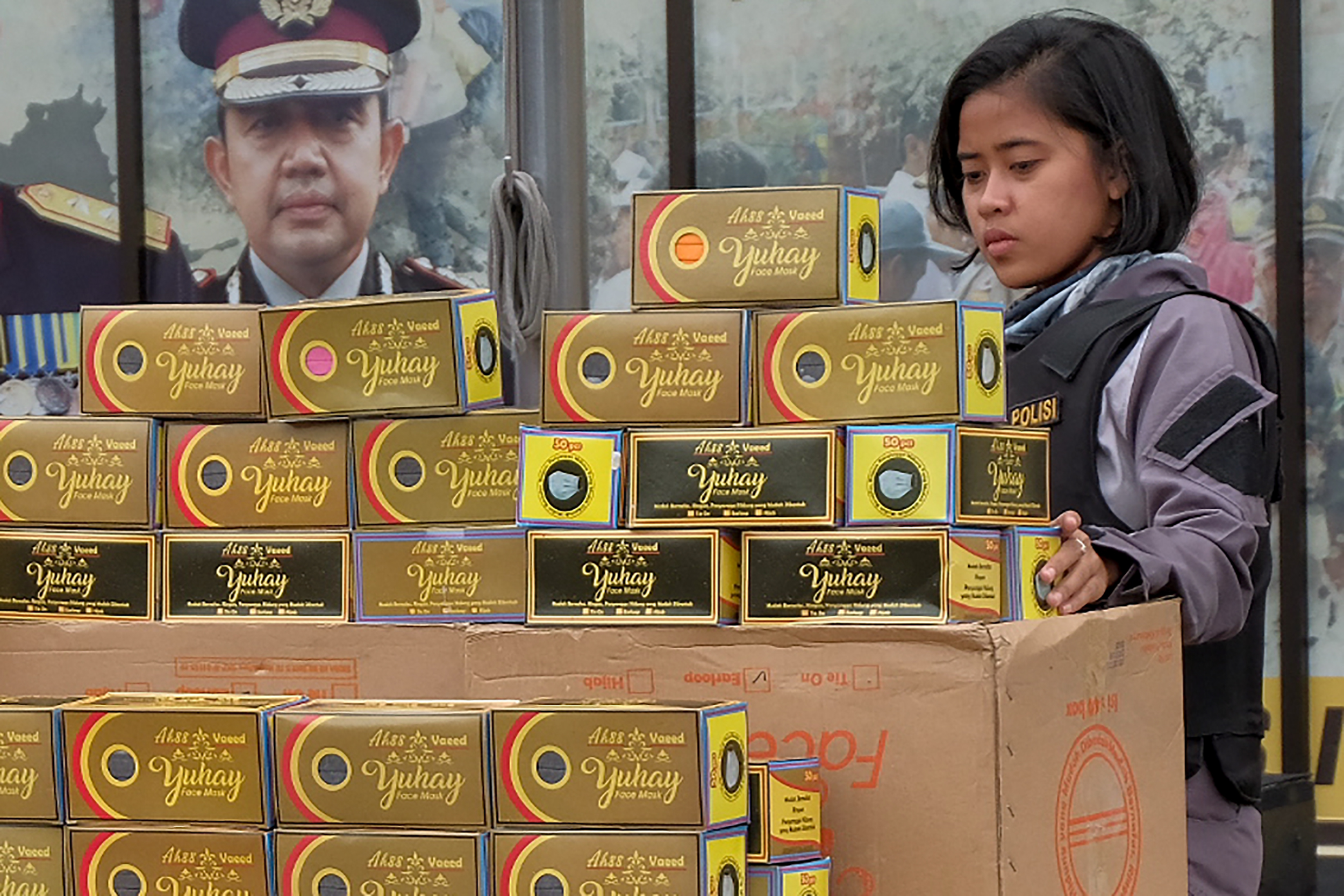 An Indonesian police officer stands next to seized boxes of face masks prior to a press conference at the North Jakarta police headquarters in Jakarta on Friday.