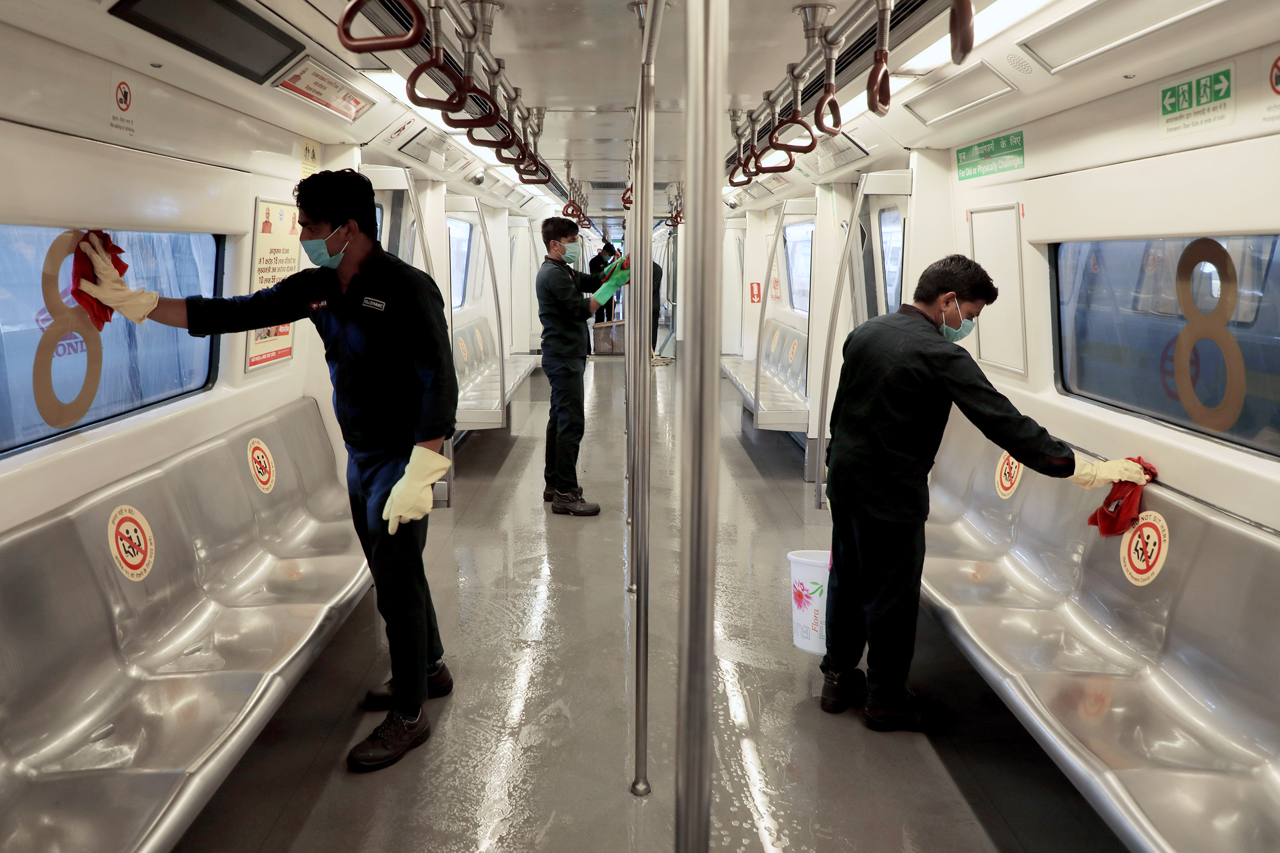 Workers disinfect the interior of a Delhi metro rail carriage at the Khyber Pass metro depot ahead of the resumption of services in New Delhi on Sunday, September 6.