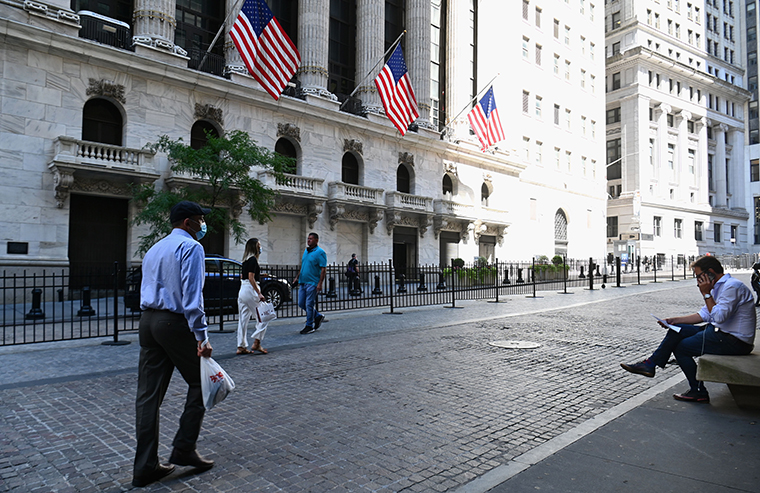 People walk past The New York Stock Exchange on August 3, 2020 on Wall Street in New York City.