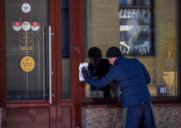 A man cleans a cafe door amid concerns of the coronavirus in central Moscow on March 25.