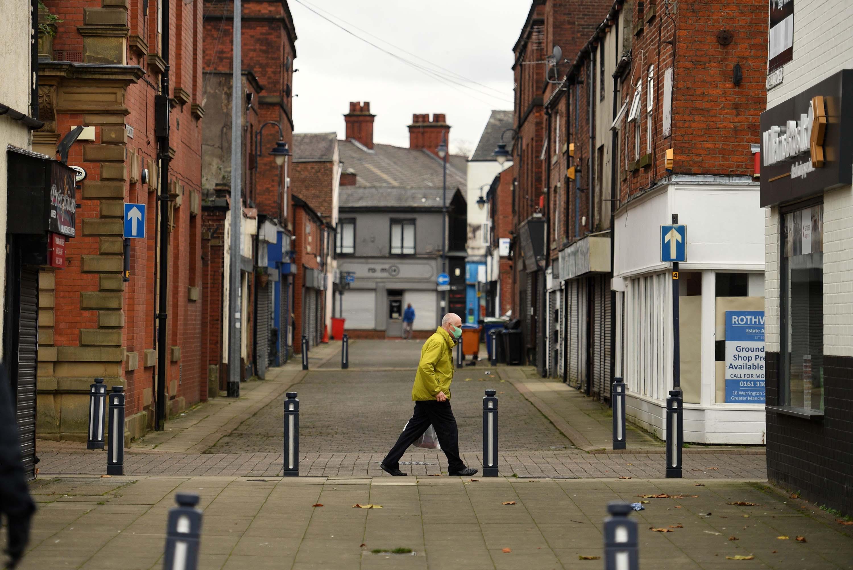 A man walks along a street in Ashton-under-Lyne, England, amid a second nationwide lockdown on November 11.