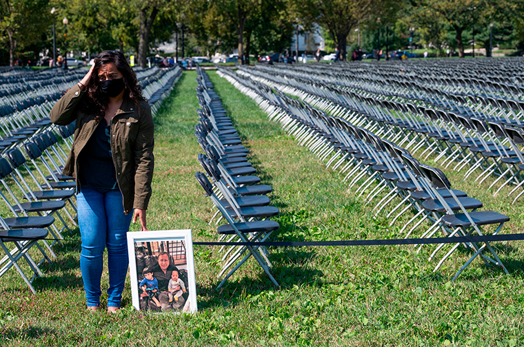 Naeha Quasba reacts as she holds a picture of her father, Ramasha Quasba, who died from coronavirus as she stands near empty chairs on display to represent the 200,000 lives lost due to COVID-19 at the National COVID-19 Remembrance, on the ellipse behind the White House in Washington, DC, on October 4, 2020.