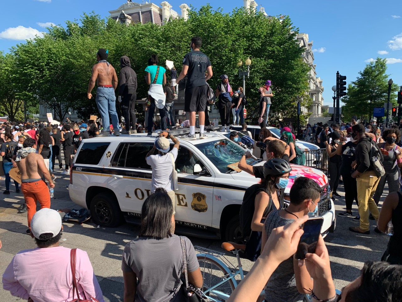 Protesters standing atop three Secret Service vehicles that were damaged outside the White House on May 30, 2020.