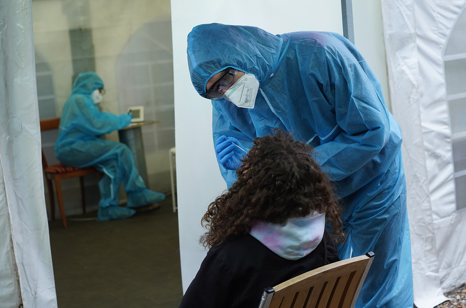A medical worker takes a nose swab sample from a young woman for a Covid-19 test in Berlin, on January 7.