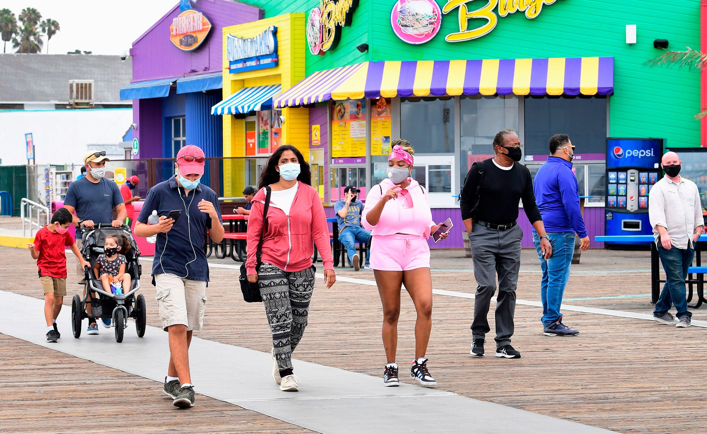 People wear facemasks while visiting Santa Monica Pier on June 26 in Santa Monica, California.