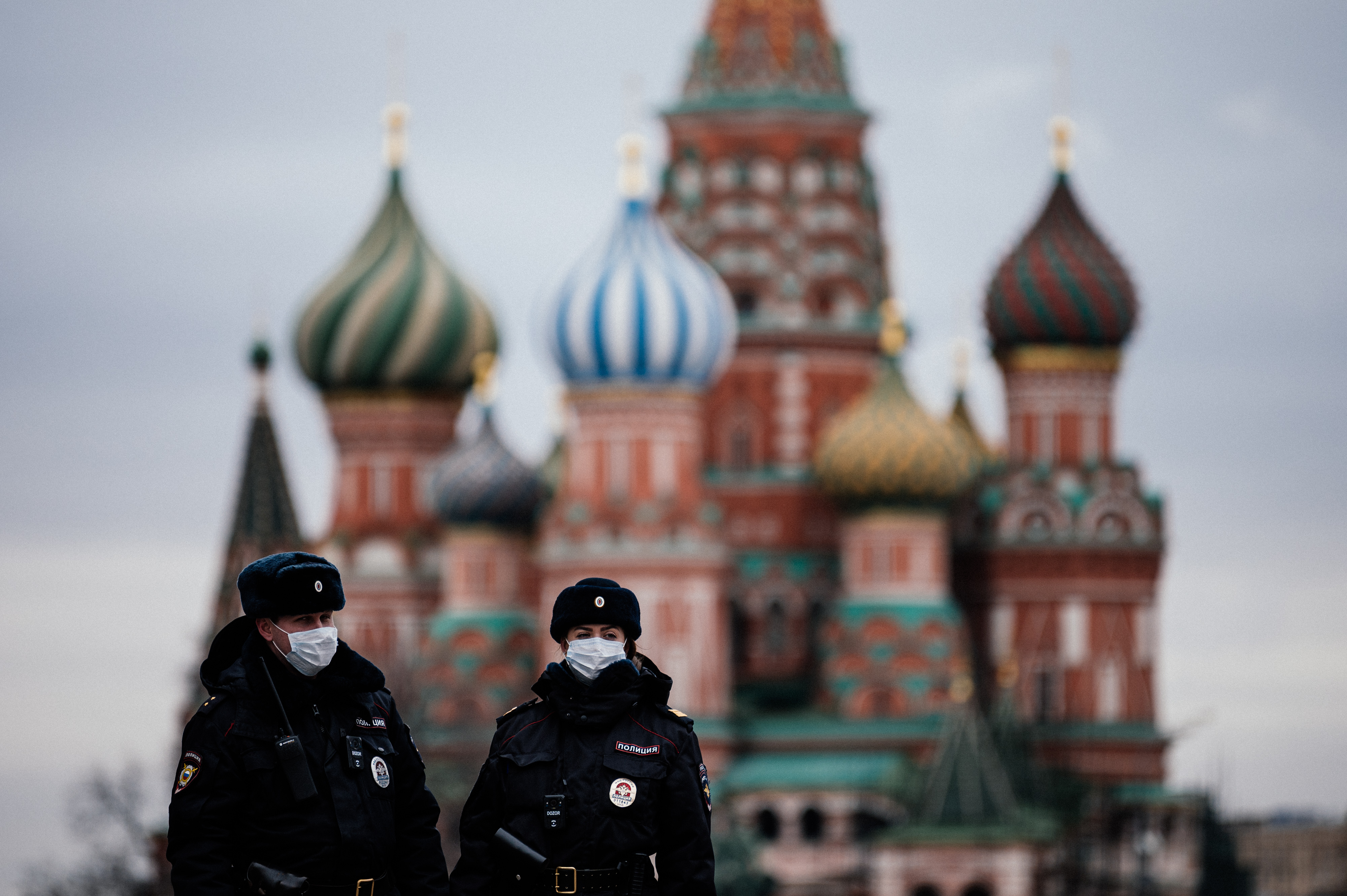Russian police officers patrol the deserted Red square in front of Saint Basil's Cathedral in Moscow on Monday, March 30, as the city and its surrounding regions imposed lockdowns.