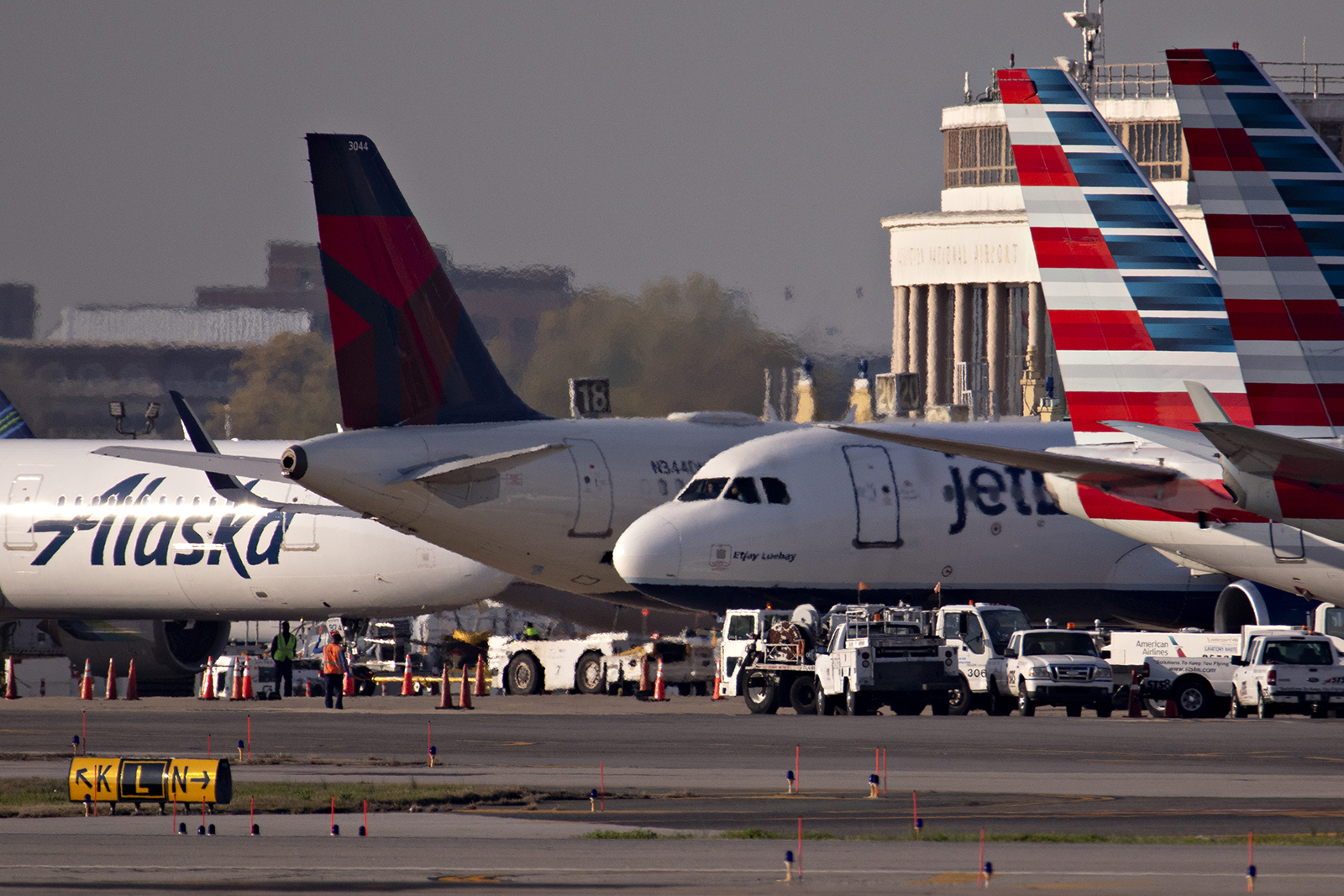 A JetBlue Airways Corp. plane taxis next to American Airlines Group Inc., Delta Air Lines Inc., and Alaska Airlines Inc. aircraft at Reagan National Airport (DCA) in Arlington, Virginia, on Monday, April 6.