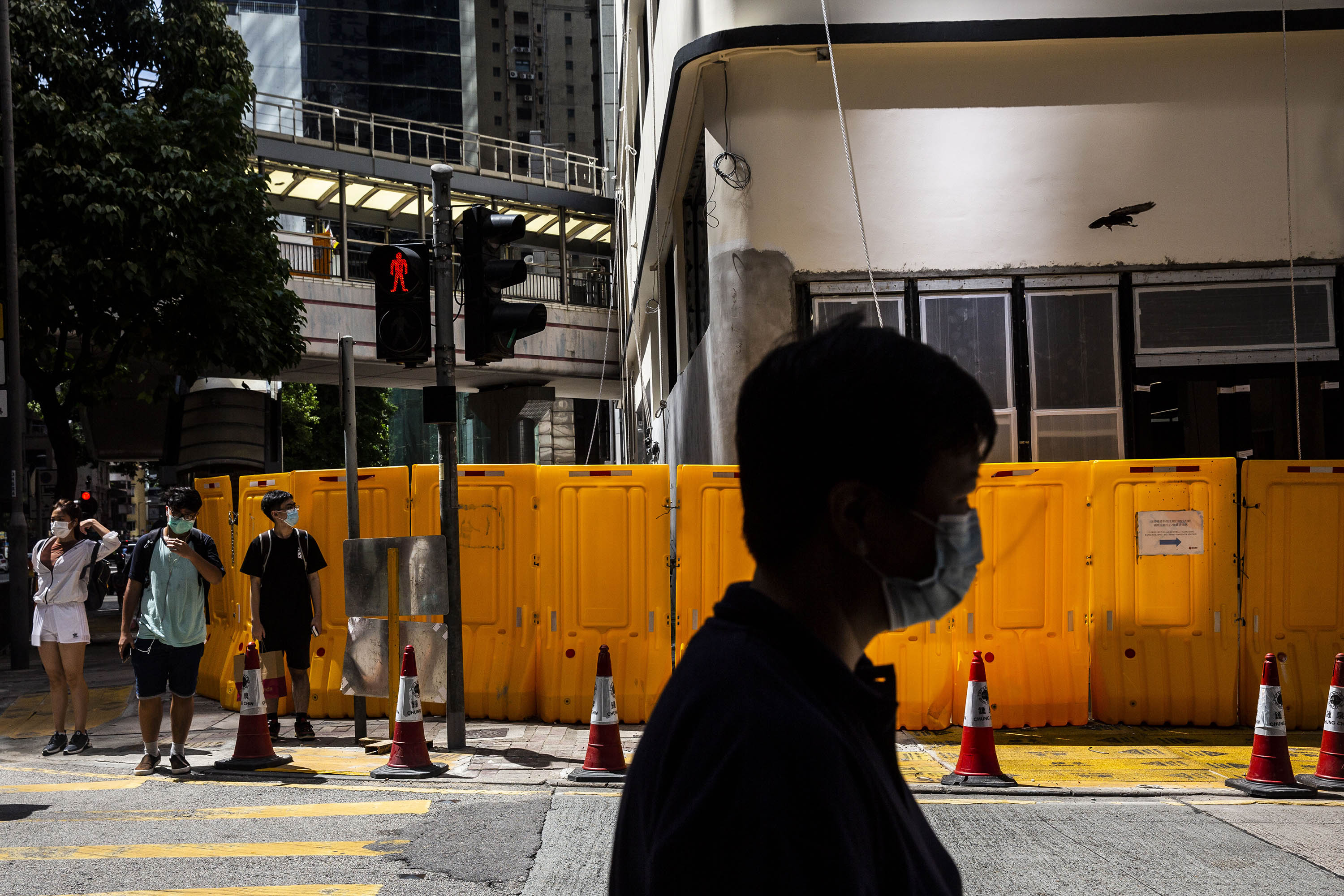 Pedestrians wearing masks are seen in Hong Kong's Central district on August 6.