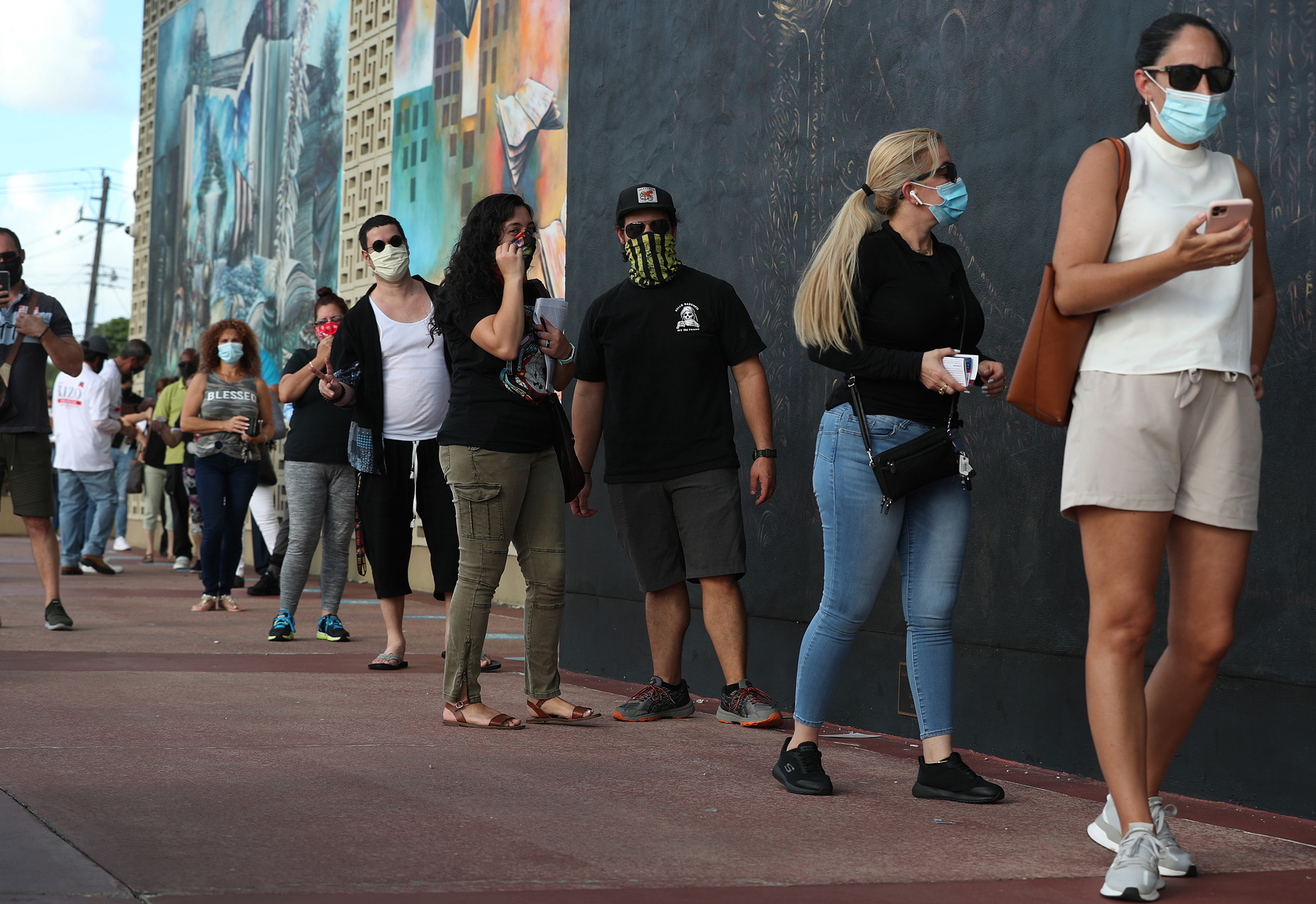 Voters wait in line to cast their early ballots at the Hialeah John F. Kennedy Library polling station on October 28 in Hialeah, Florida.