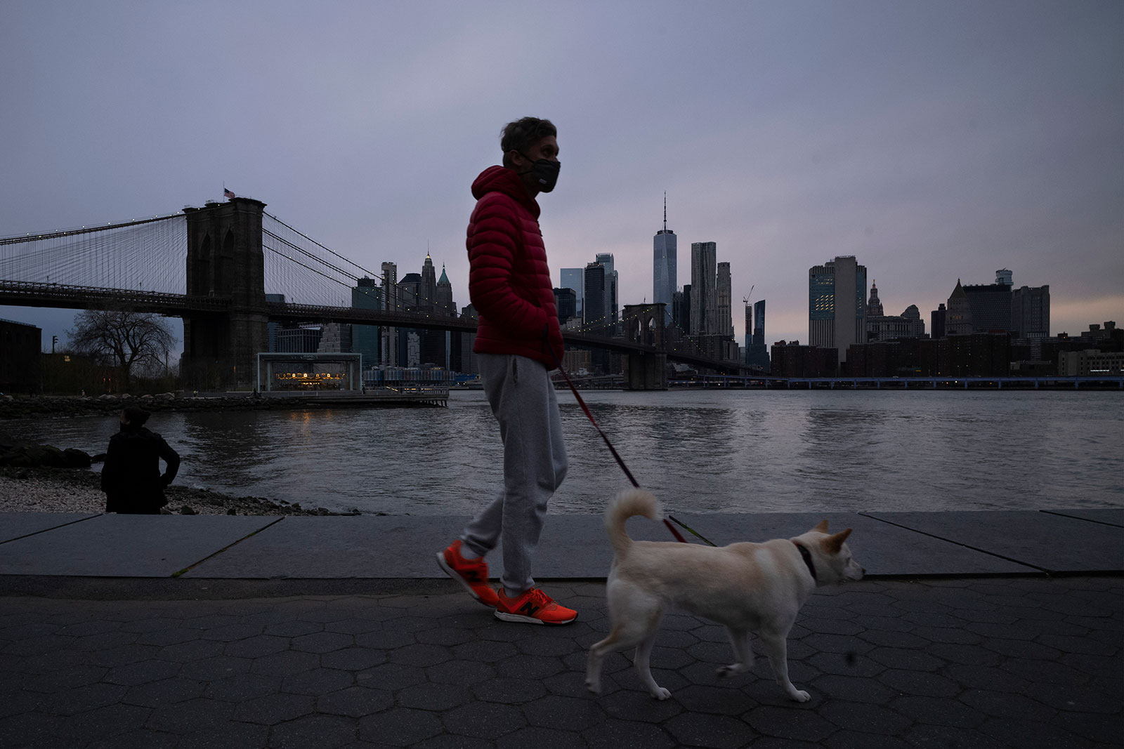 A man wears a mask while walking his dog in Brooklyn Bridge Park on Tuesday, April 14.