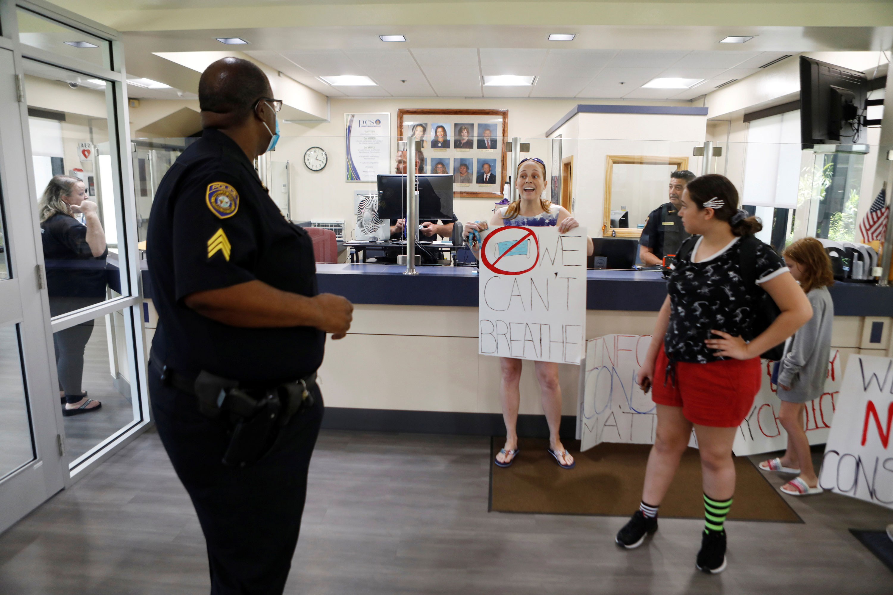 A parent confronts a police officer while protesting against wearing masks in schools before the special called school board workshop at the Pinellas County Schools Administration Building in Largo, Florida, on August 9.