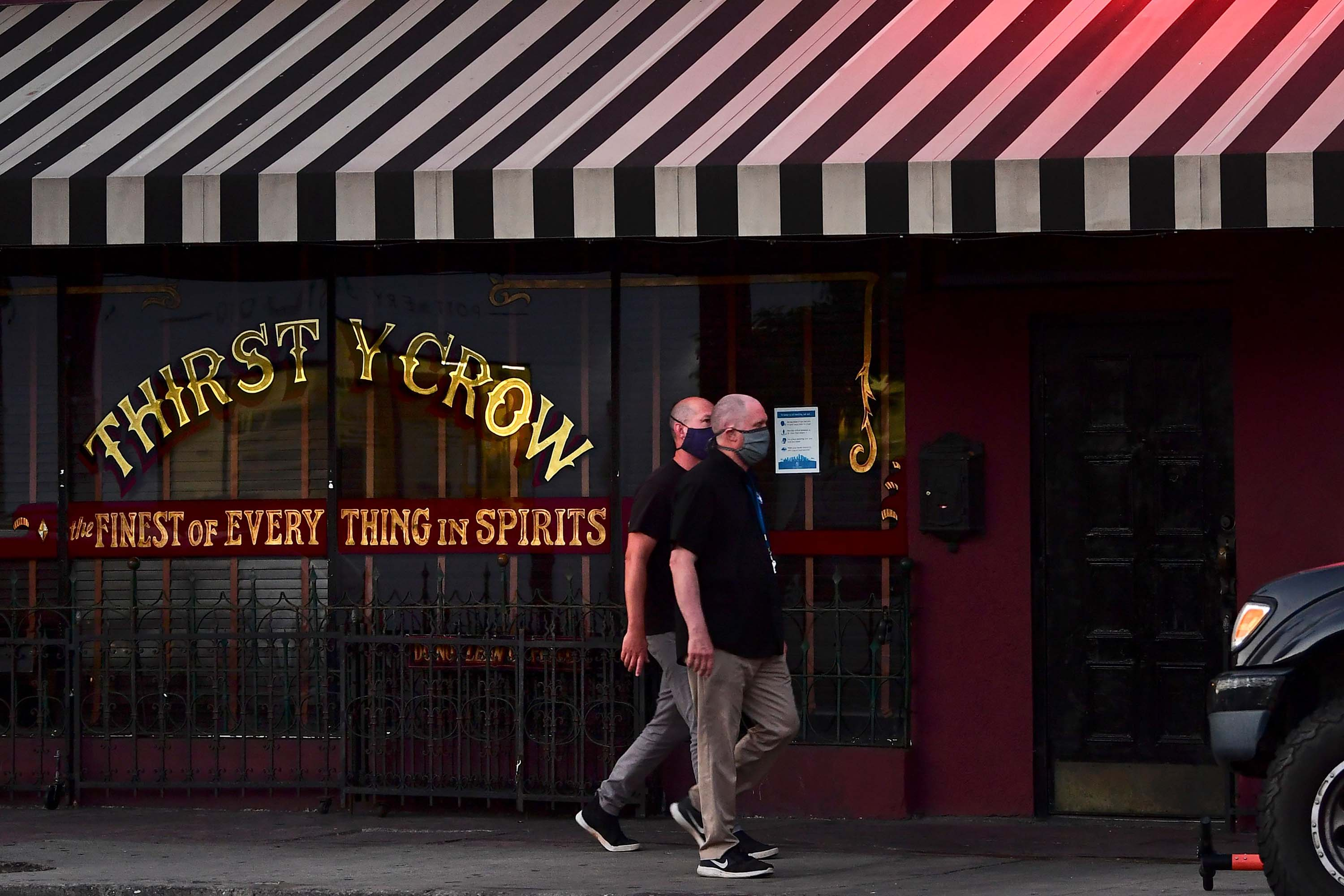 People wearing face masks walk past a closed bar in Los Angeles, California on June 29.
