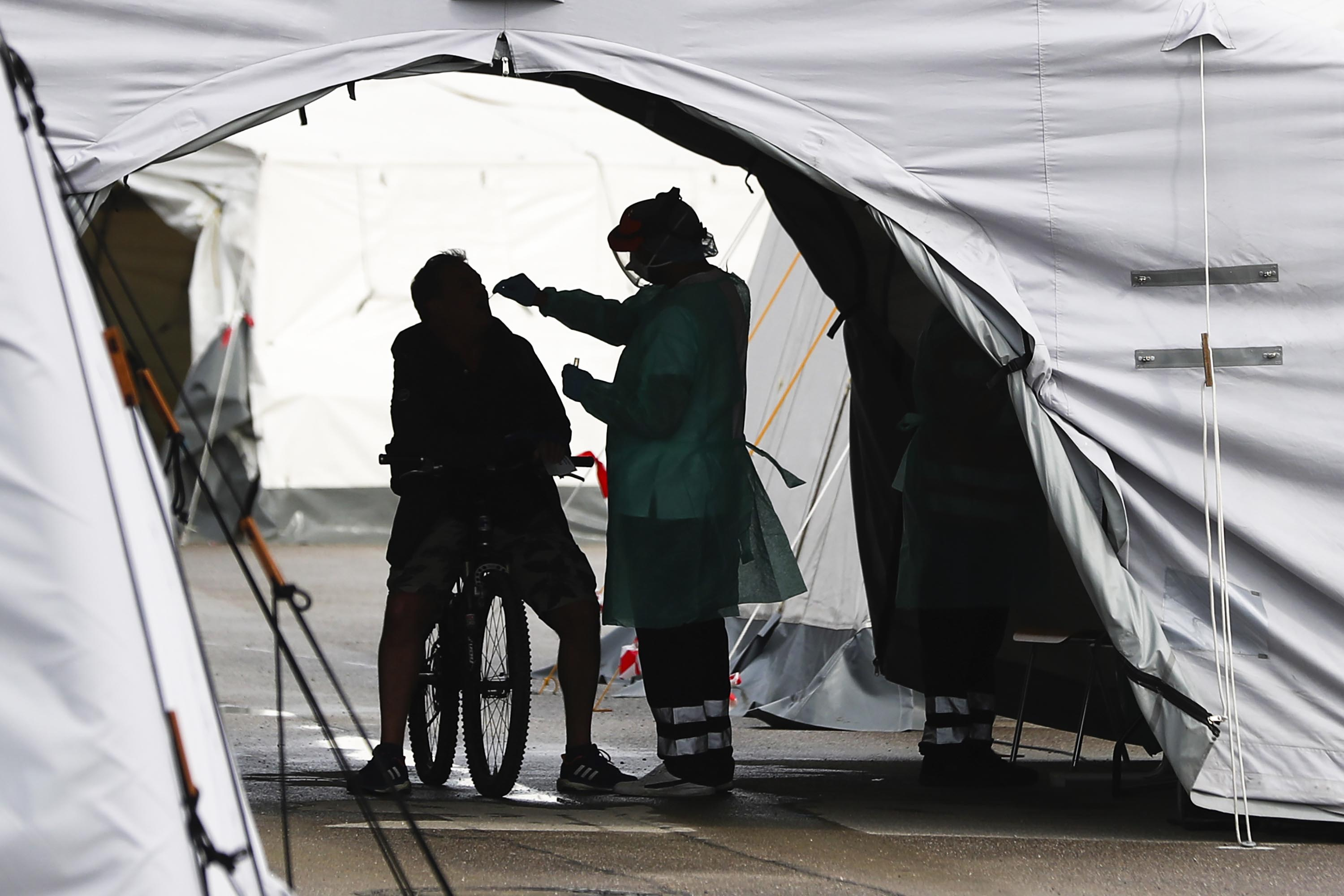A medical worker takes a sample at a coronavirus test station at the Oktoberfest Theresienwiese grounds in Munich, Germany, on September 24.