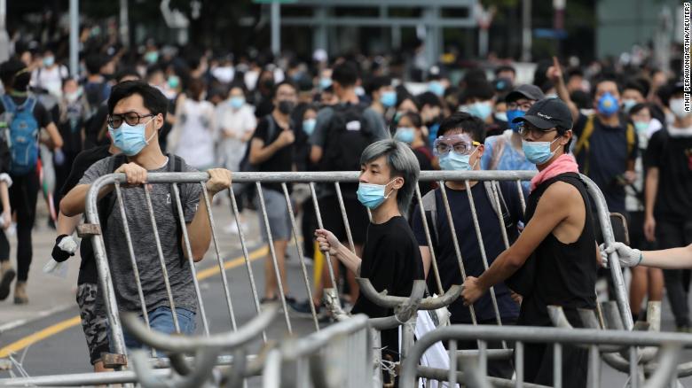 Demonstrators remove metal barricades in Hong Kong.