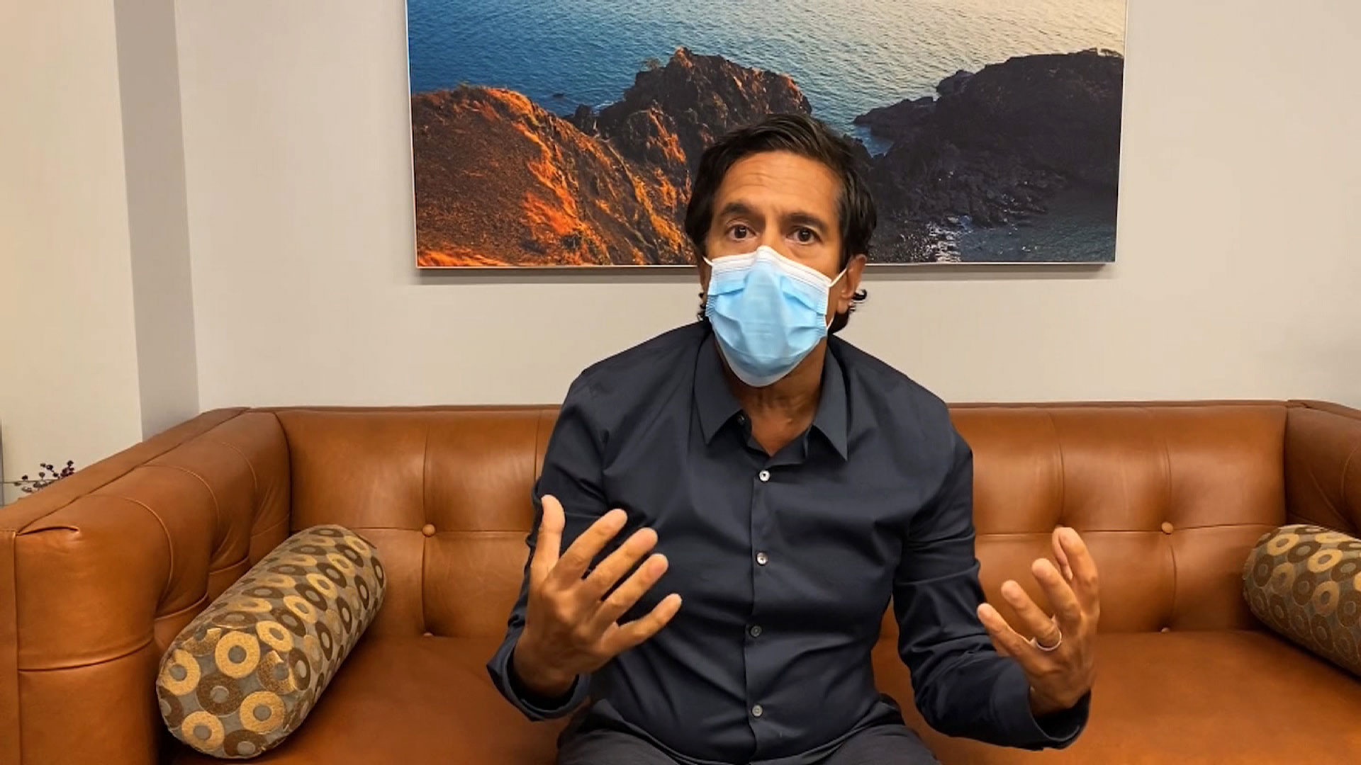 Dr. Sanjay Gupta shows the correct way to wear a face mask during CNN's global coronavirus town hall on August 6.