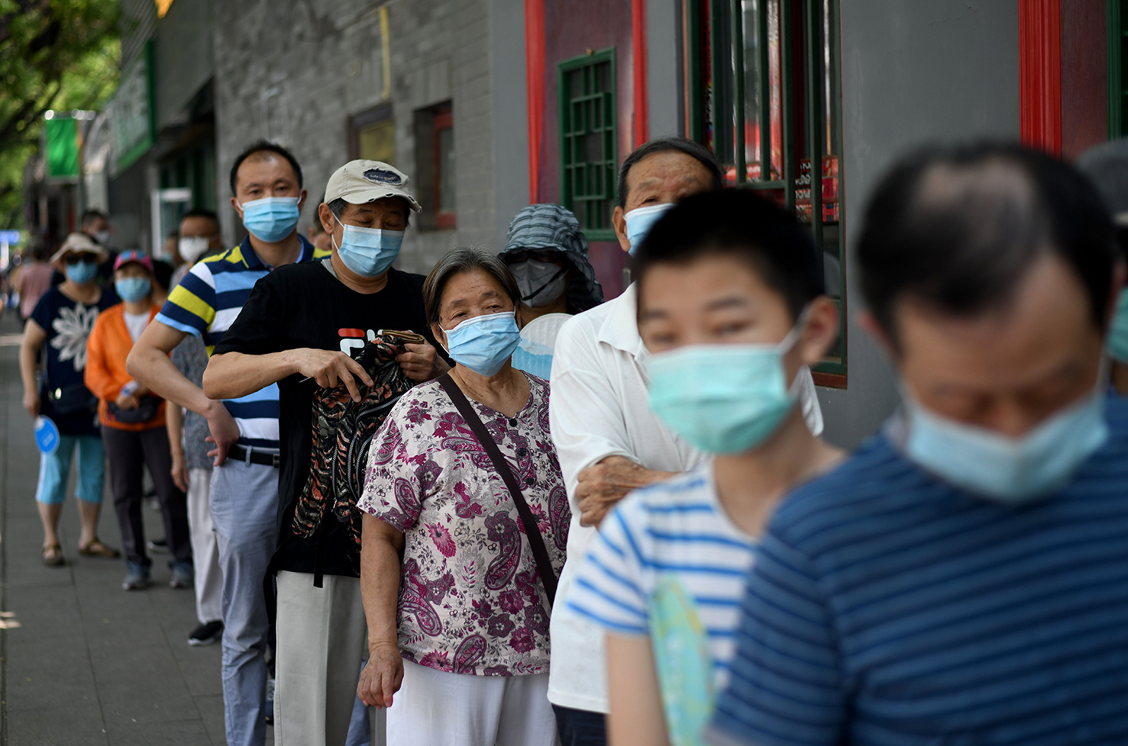 People wearing face masks queue to take a swab test during mass testing for the Covid-19 in Beijing on June 21.