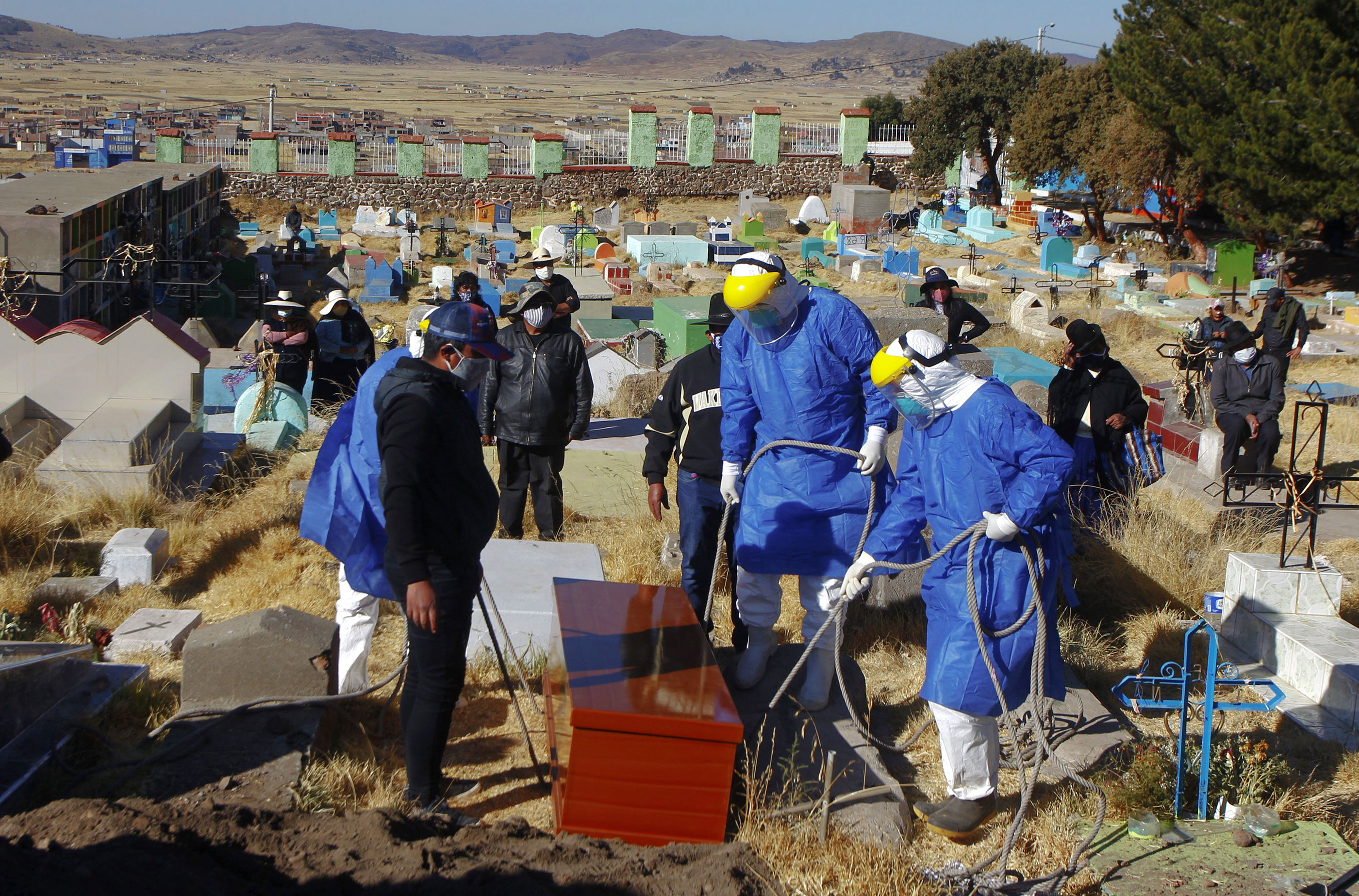 Workers in protective suits prepare to lower a coffin into the ground during the burial of a Covid-19 victim in the remote highland village of Acora, Peru, on August 9, 2020.