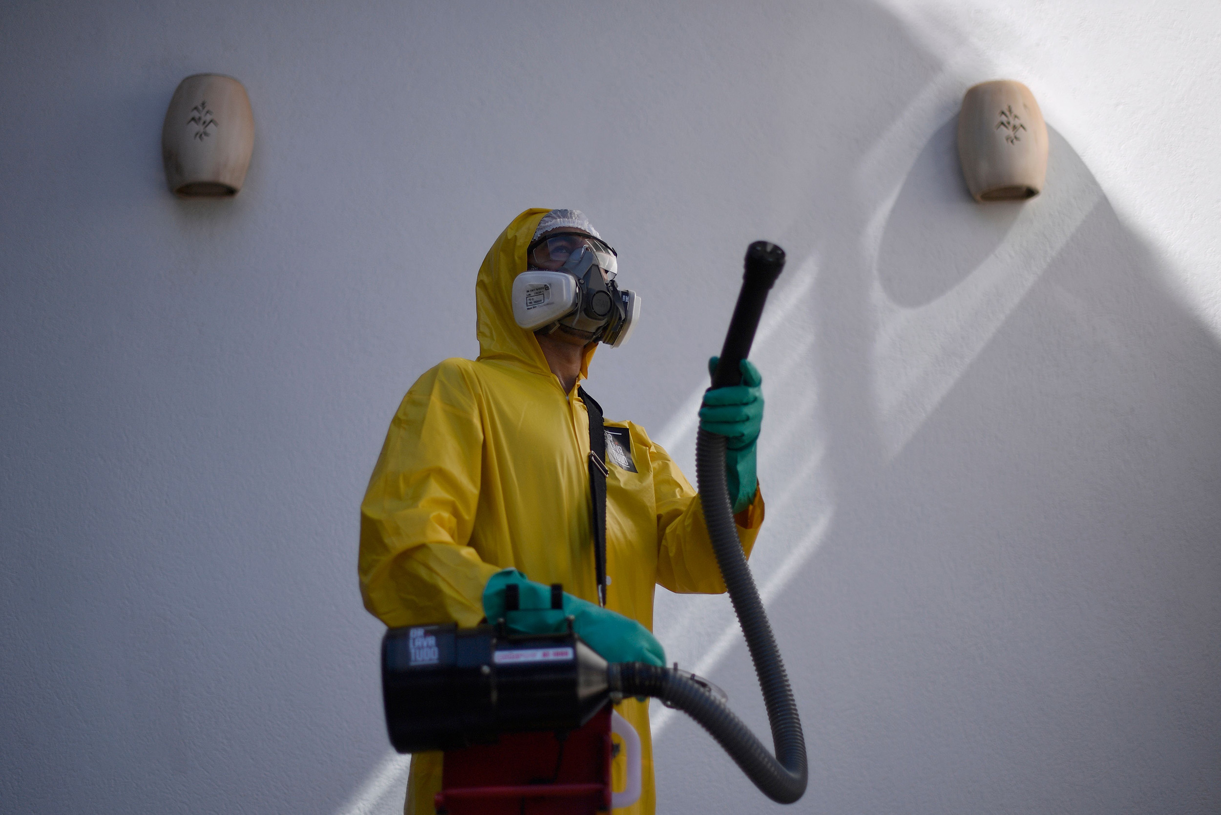 An employee of a private company sanitizes against the spread of the novel coronavirus at a house in Belo Horizonte, Brazil, on June 26.