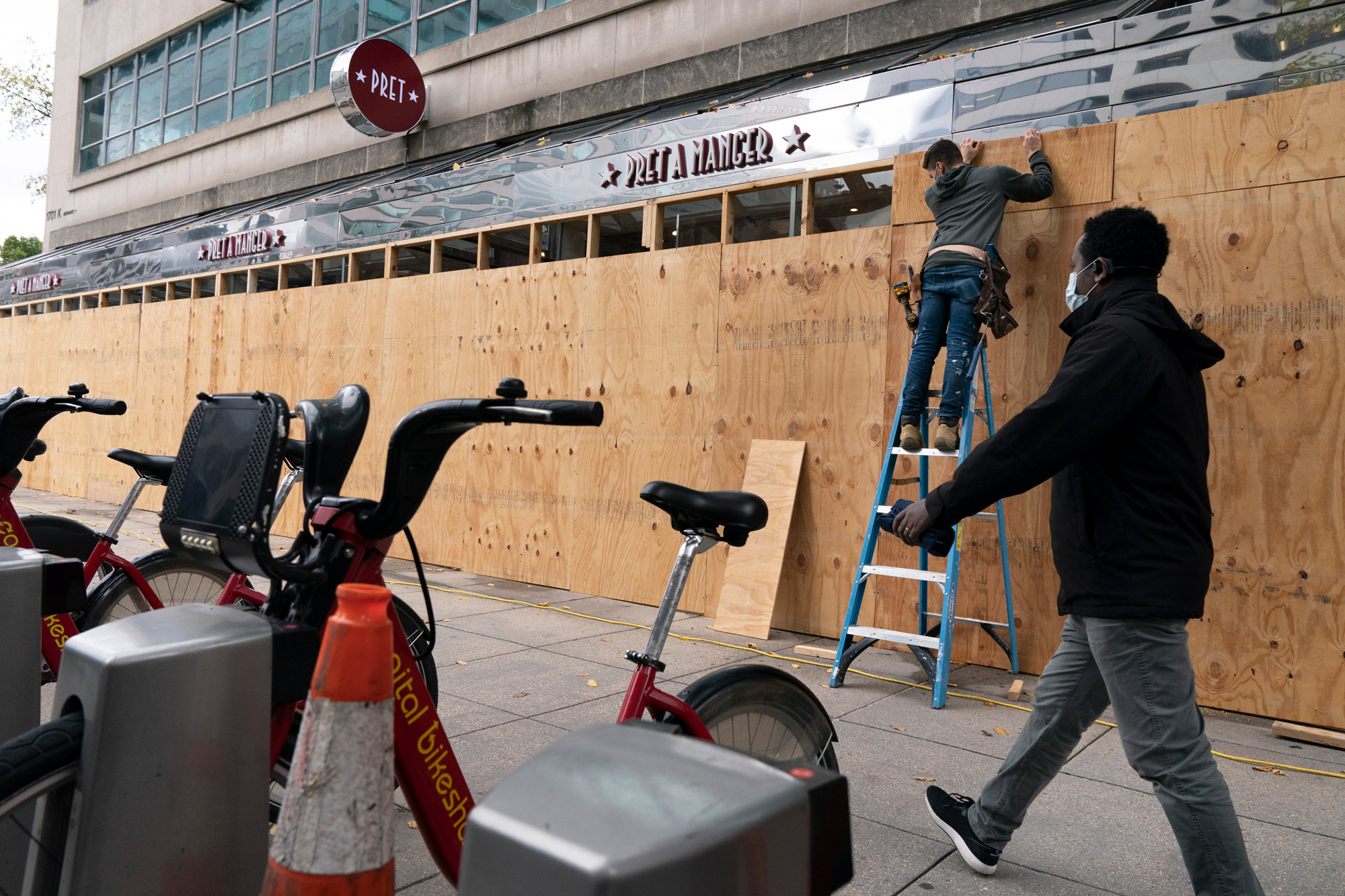 A pedestrian passes work being done to board up a Pret A Manger restaurant along K Street on October 30.
