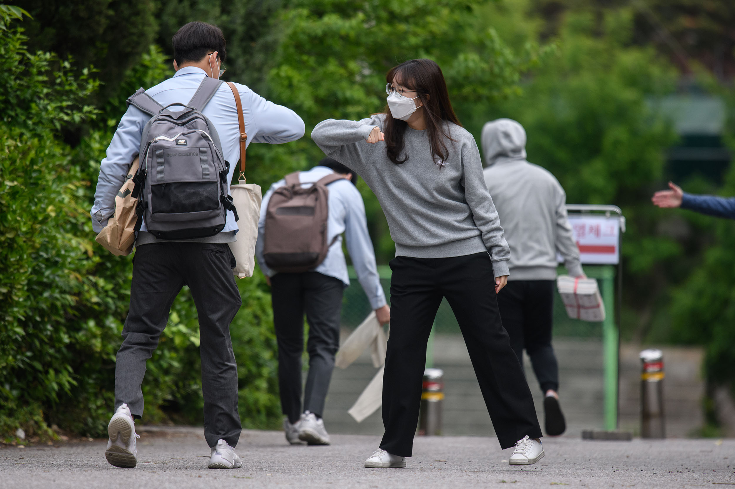 A staff member greets a student at a high school in Seoul, South Korea, on May 20.