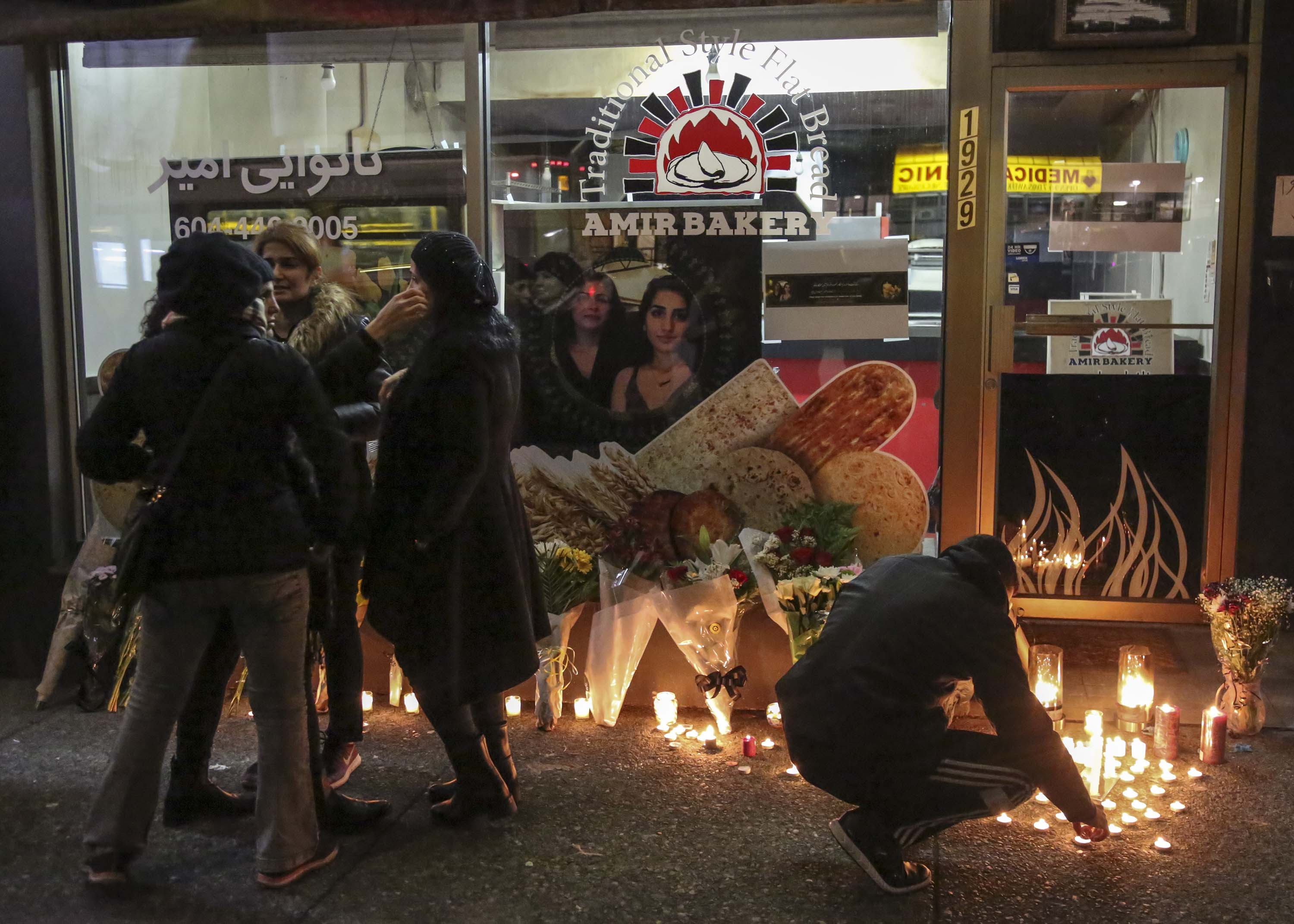 Mourners attend a vigil for crash victims outside the Amir Bakery in North Vancouver, Canada on January 8.