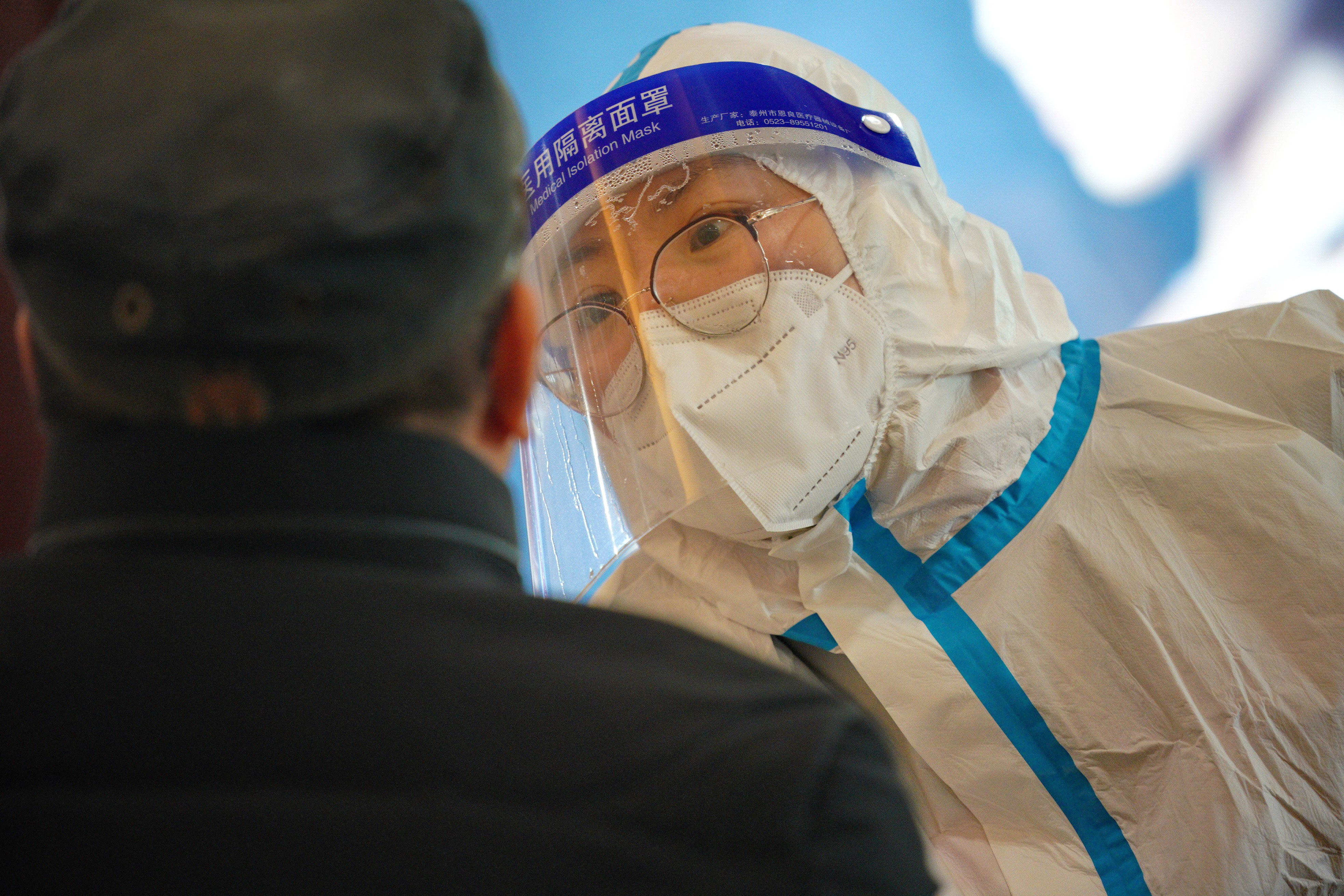 A medical worker collects a swab sample from a person at a Covid-19 testing site in the Qiaoxi District of Shijiazhuang, China, on January 20.